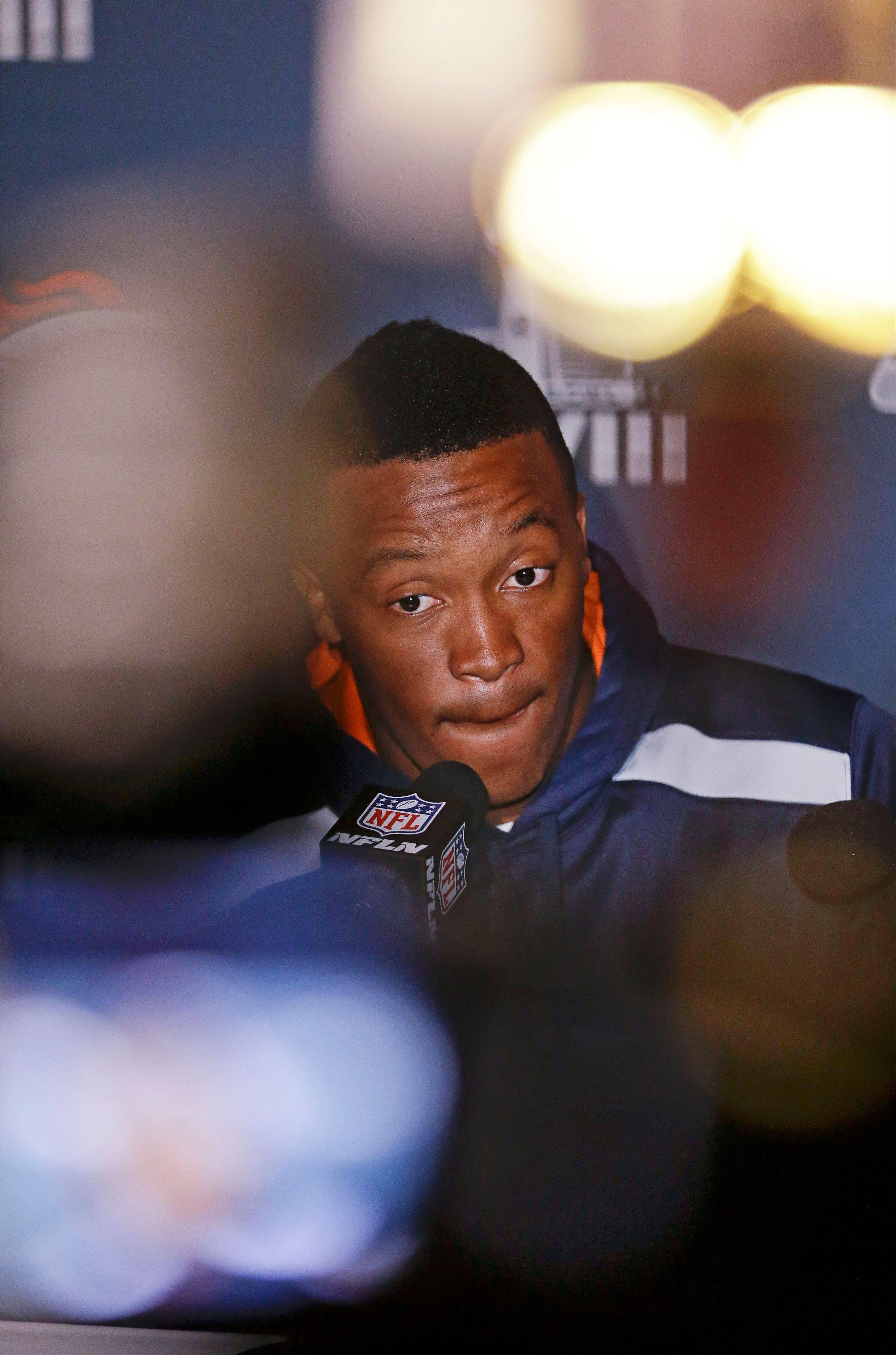 Denver Broncos wide receiver Demaryius Thomas is seen between lights and cameras as he talks with reporters during a news conference Monday, Jan. 27, 2014, in Jersey City, N.J. The Broncos are scheduled to play the Seattle Seahawks in the NFL Super Bowl XLVIII football game Sunday, Feb. 2, in East Rutherford, N.J.