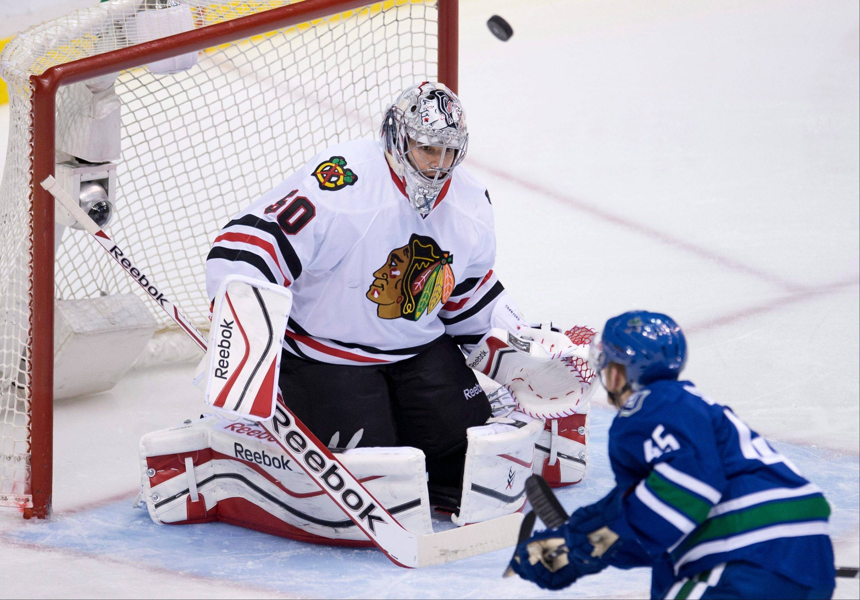 Vancouver Canucks center Jordan Schroeder (45) tries to get a shot past Chicago Blackhawks goalie Corey Crawford (50) during the first period of an NHL hockey game Wednesday, Jan. 29, 2014, in Vancouver, British Columbia.