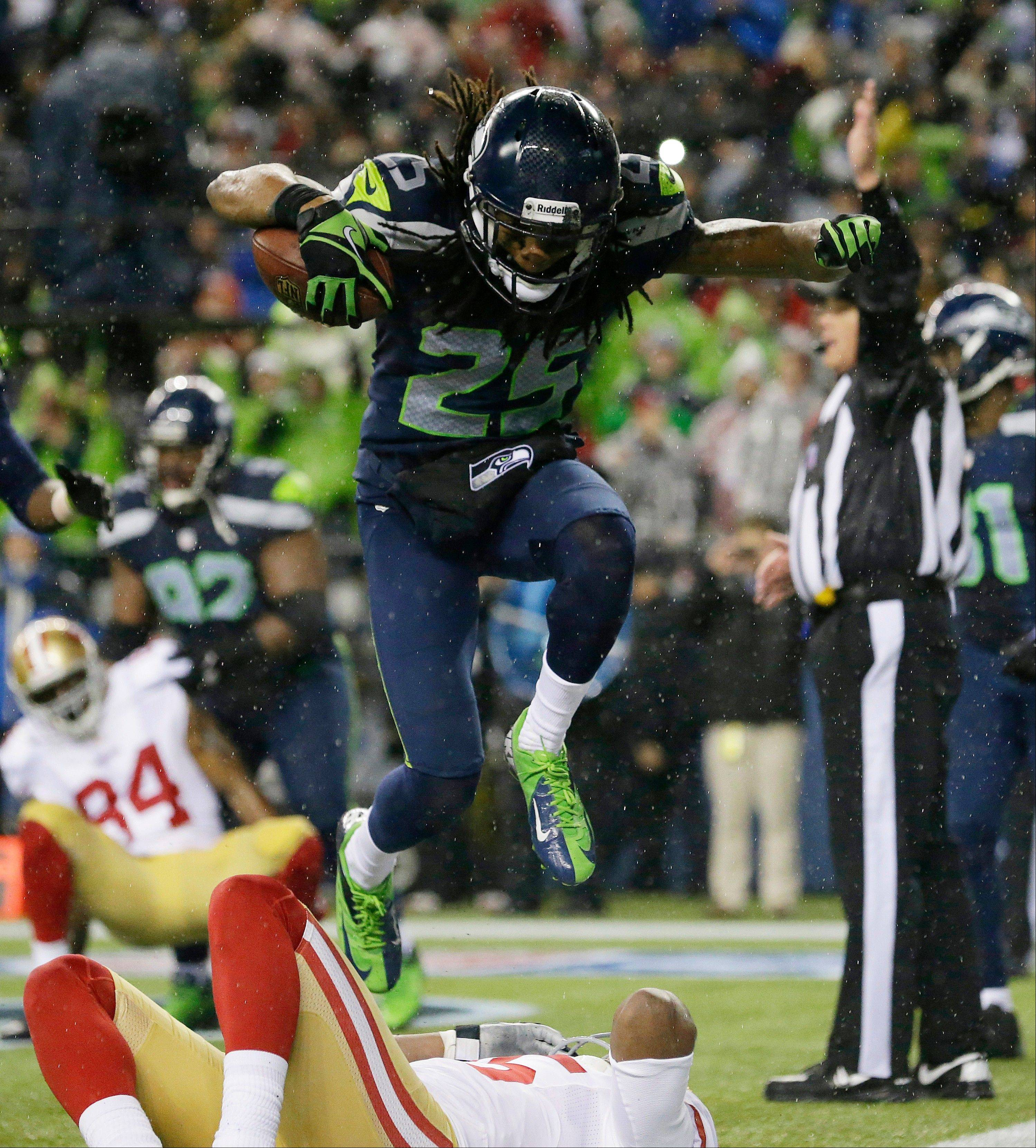 Seattle Seahawks' Richard Sherman jumps over San Francisco 49ers' Michael Crabtree as Sherman celebrates his interception in the second half of an NFL football game, Sunday, Dec. 23, 2012, in Seattle.