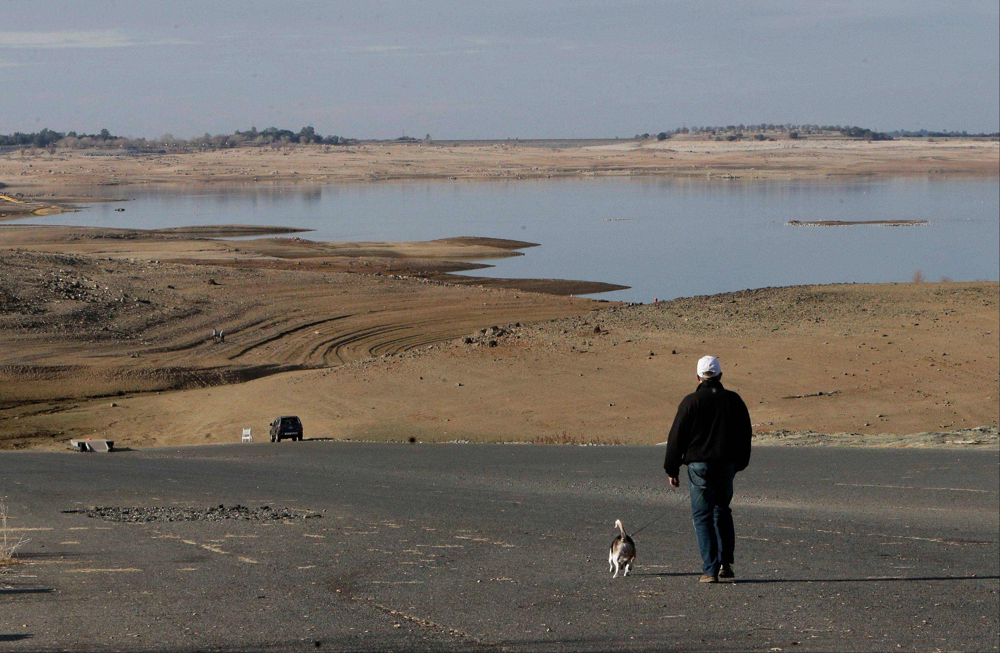 A visitor to Folsom Lake, Calif., walks his dog down a boat ramp that is now several hundred yards away from the waters' edge.