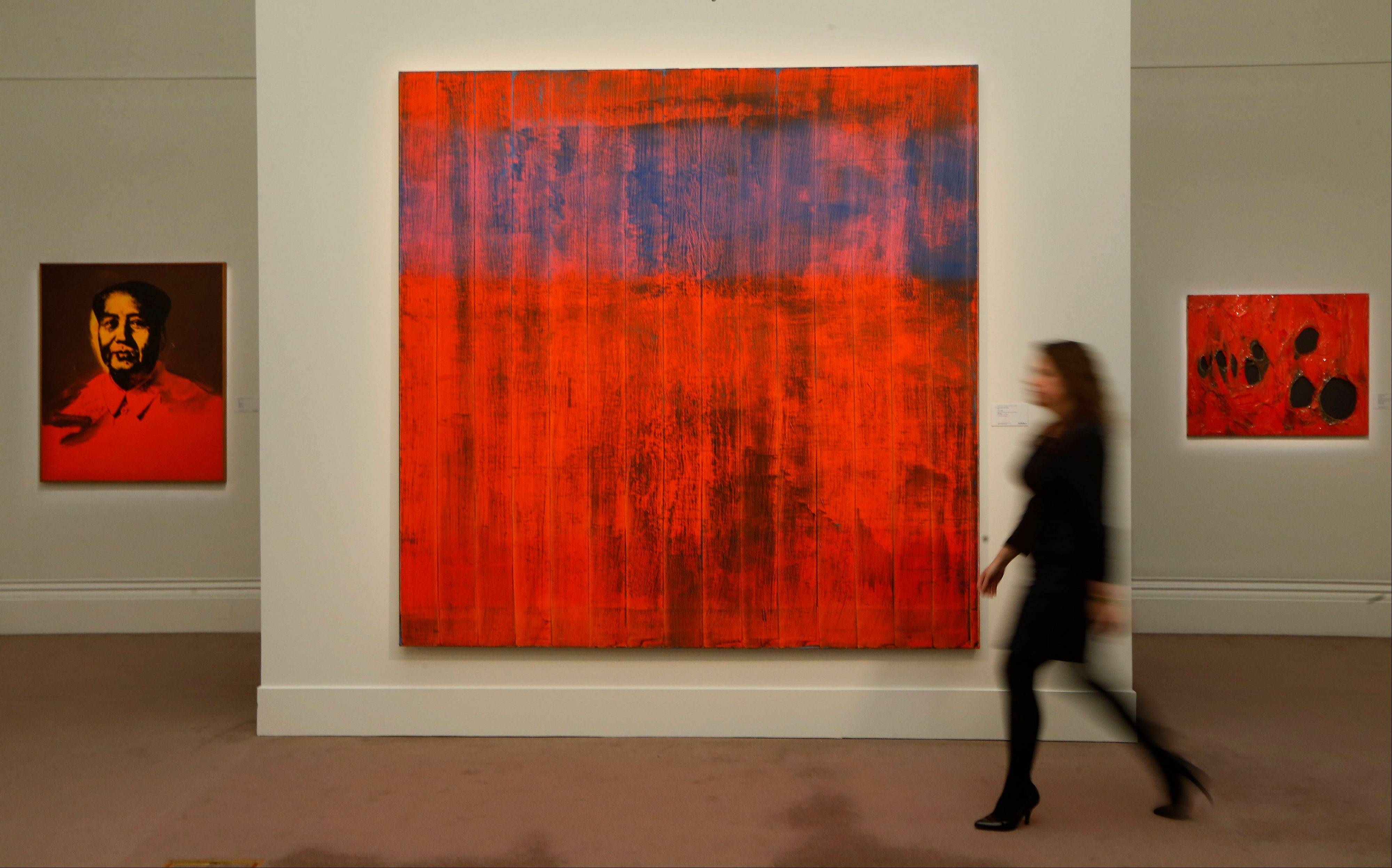 "A Sotheby's employee poses for photographers with ""Wand"" by Gerhard Richter, center, ""Mao"" by Andy Warhol, left, and ""Rosso Plastica"" by Alberto Burri on display at the auction house in London Wednesday."