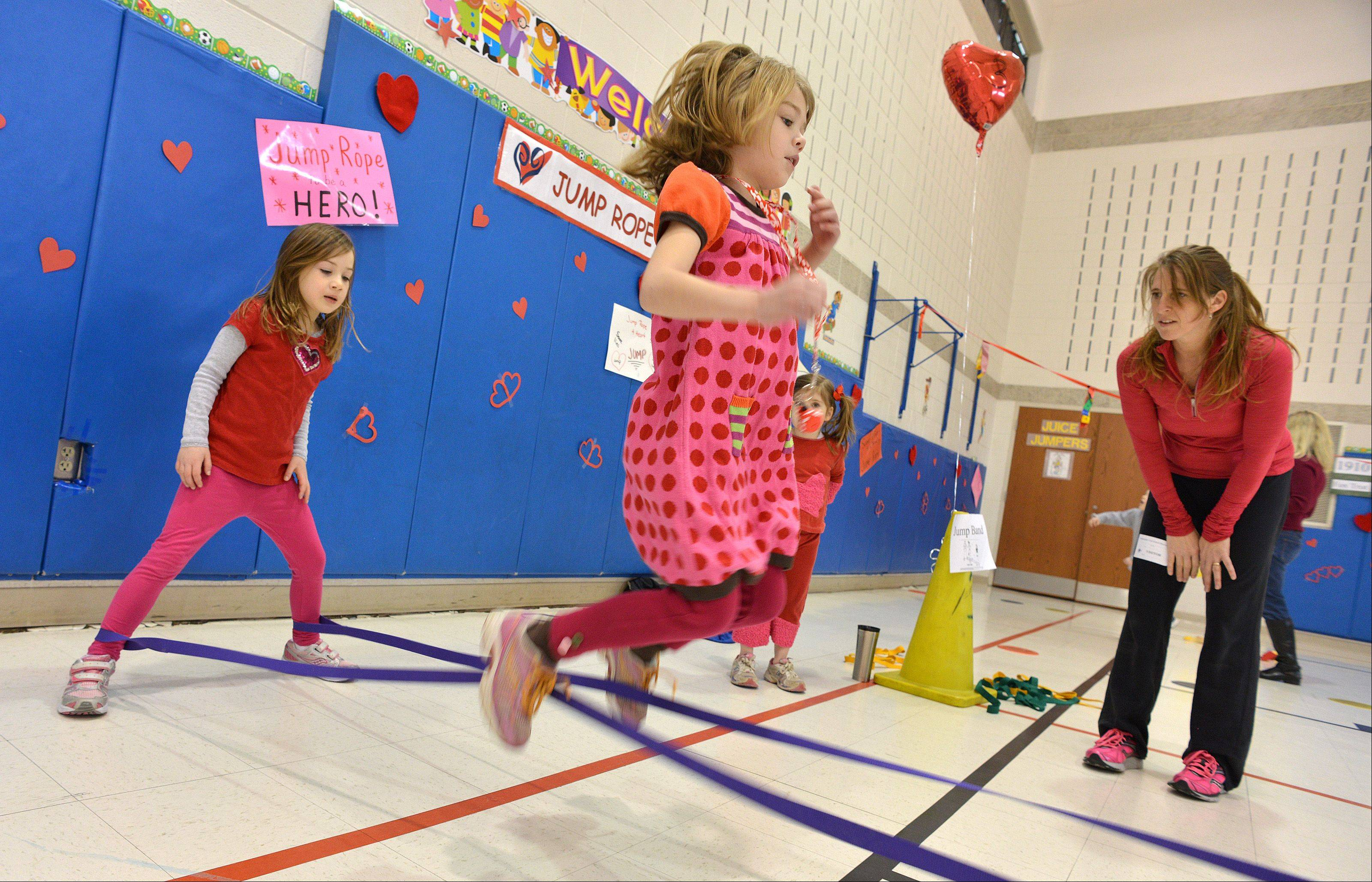 Avery Palmore, center, hops through a jump band, while Cecilia Marello, left, holds the band, and parent volunteer Theresa Ferguson watches. Students at Longfellow School in Wheaton were jumping around Friday in gym classes to raise money for the American Heart Association�s Jump Rope for Heart program.