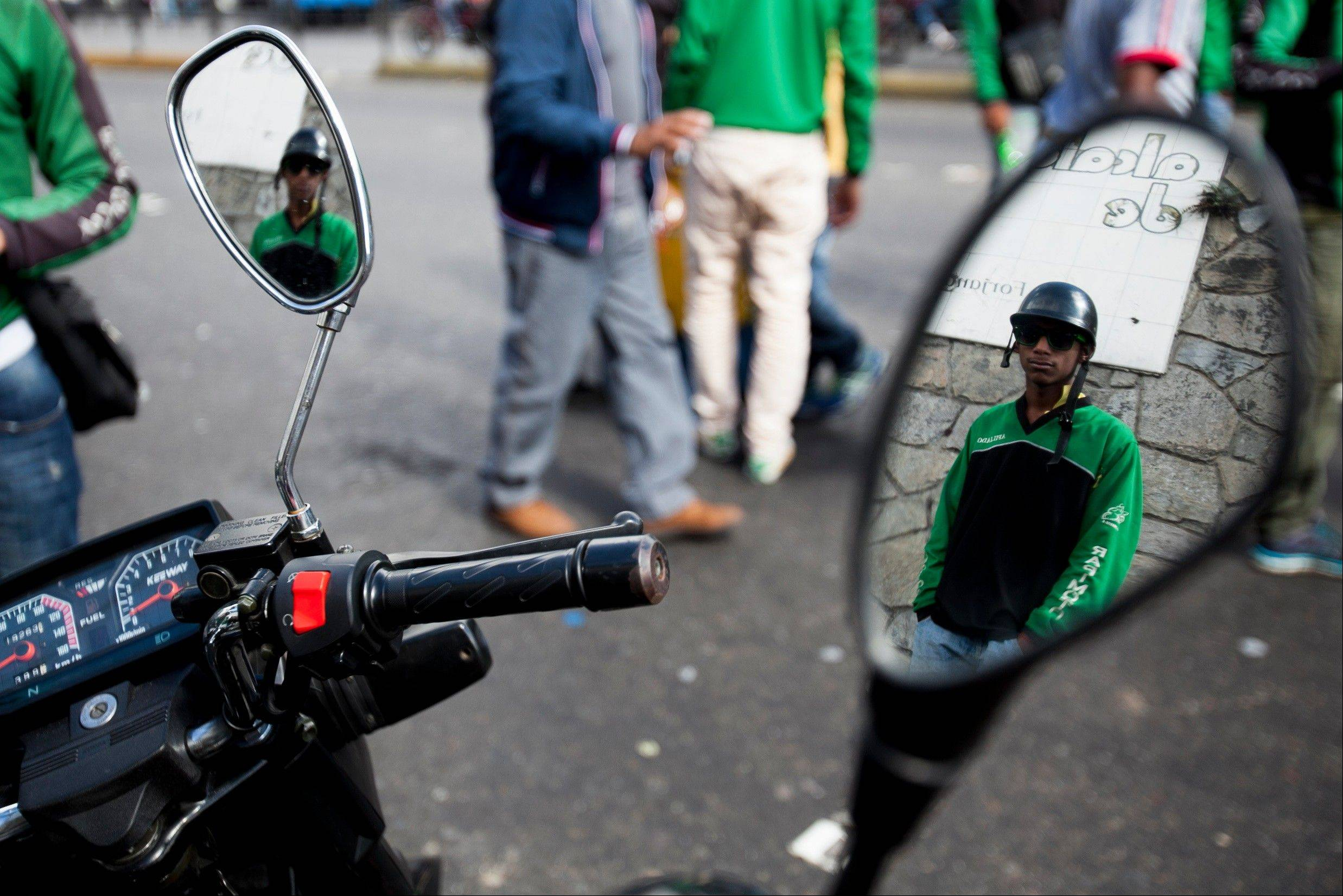 A motorcyclist is reflected in the mirror of a bike as he waits for the start of a protest Friday against a proposed nighttime curfew for two-wheelers in Caracas, Venezuela.