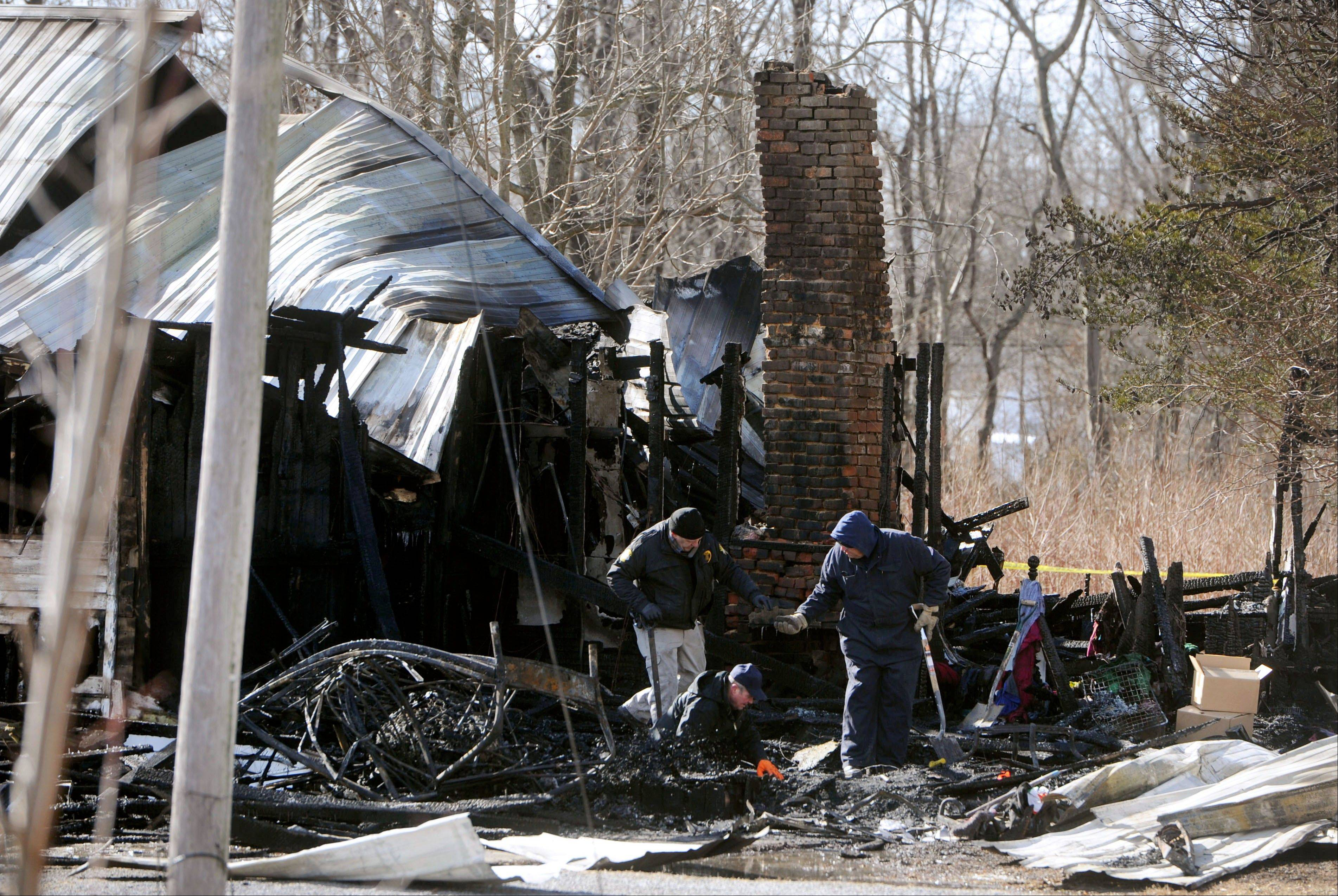 Alan Gregory, with the Kentucky Fire Marshal's office, at bottom, digs through debris Thursday Jan. 30, 2014, from a house fire that killed nine members of an 11-member family.