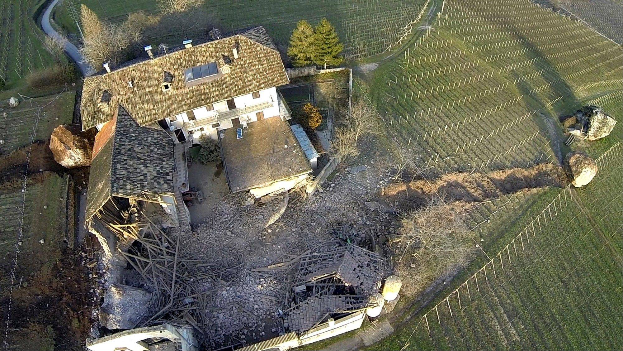 A huge boulder is seen after it missed a farm house by less than a yard, destroying the barn, and stopped in the vineyard, while the second giant boulder, at left, which detached during the same landslide on Jan. 21, stopped next to the house.