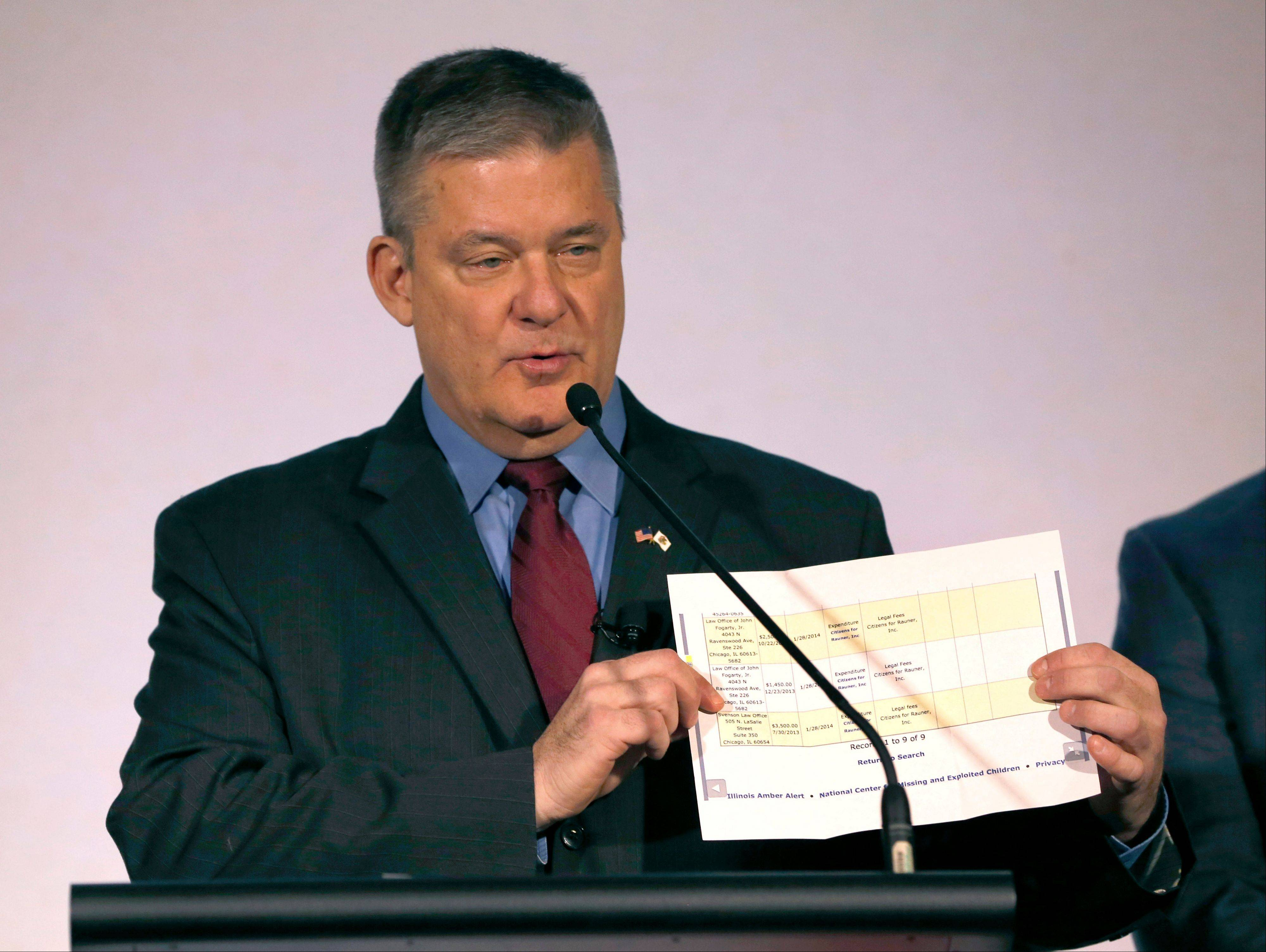 Illinois Treasurer and Republican candidate for governor Dan Rutherford holds up a copy of gubernatorial candidate Bruce Rauner's recent campaign finance report Friday after announcing his office is investigating allegations against him made by an employee he suspects was put up to it by Rauner.