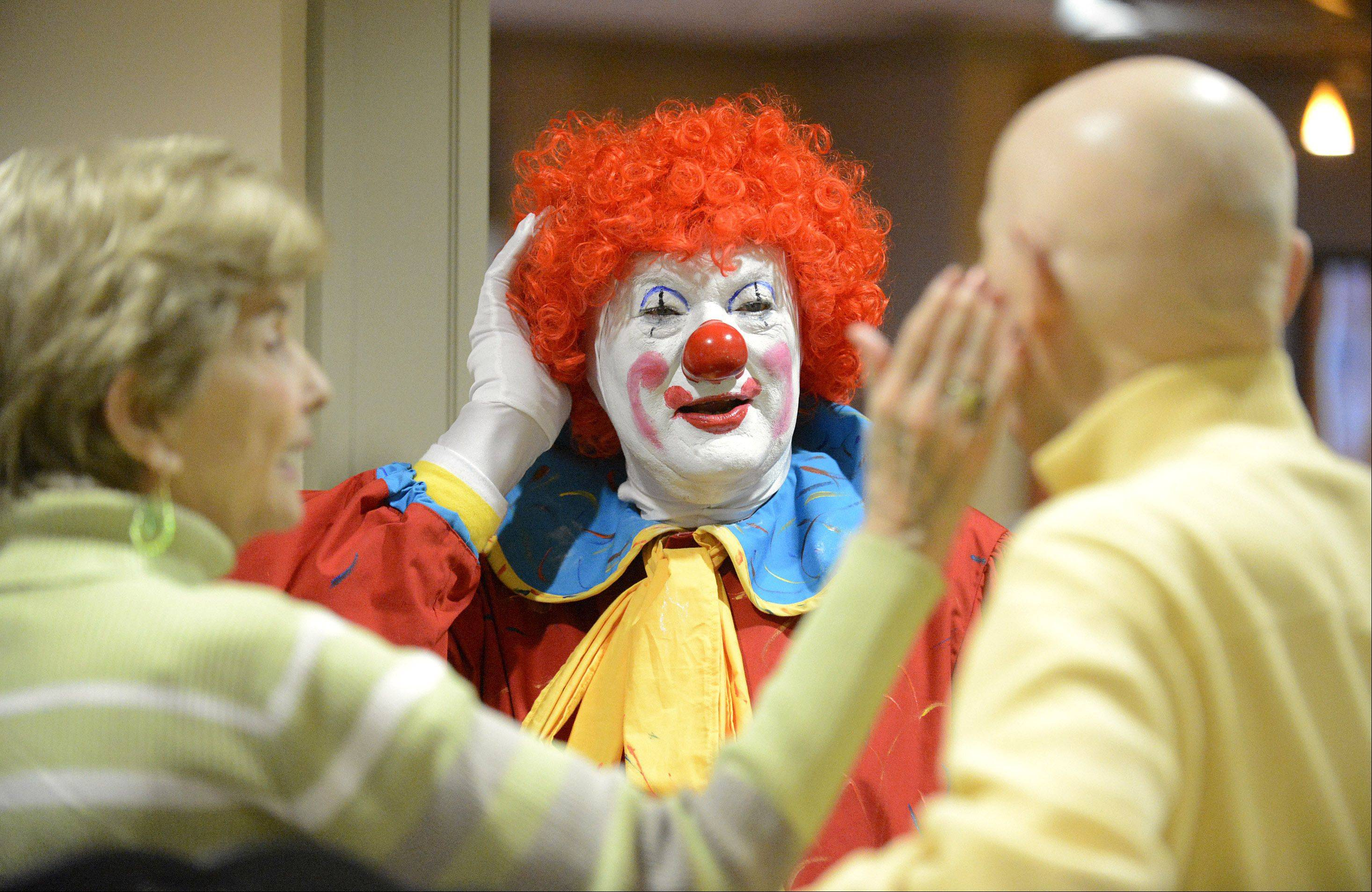 Euna Freeman jokingly compares husband Wayland's head to Polyester the clown's full head of curly, red hair. Polyester, who is Jack Kramer of Lily Lake, laughed and admitted to Euna he doesn't have much real hair under the wig. The Freemans are residents at The Holmstad retirement home in Batavia.