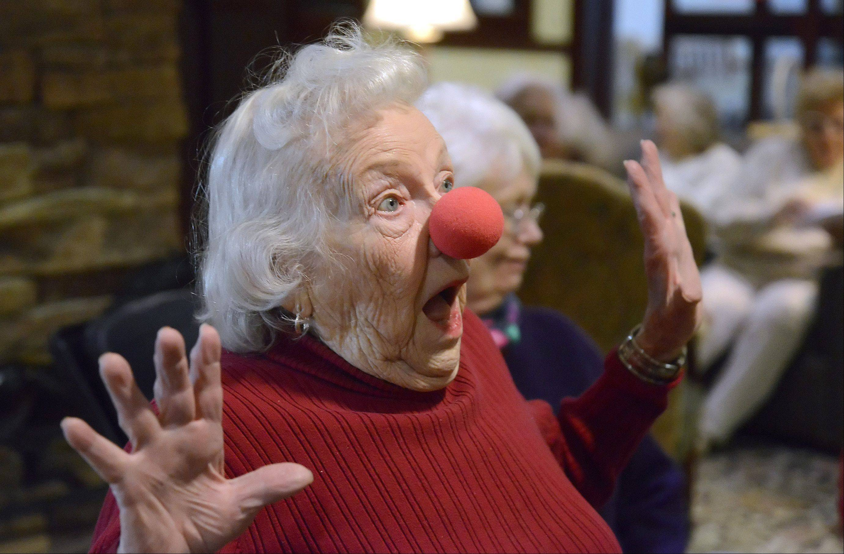 "Kally Close, 89, a resident of The Holmstad in Batavia, plays along with Polyester the clown's schtick and acts surprised after being donned with a foam nose. She told him, ""You make us happy, but you get the joy."""