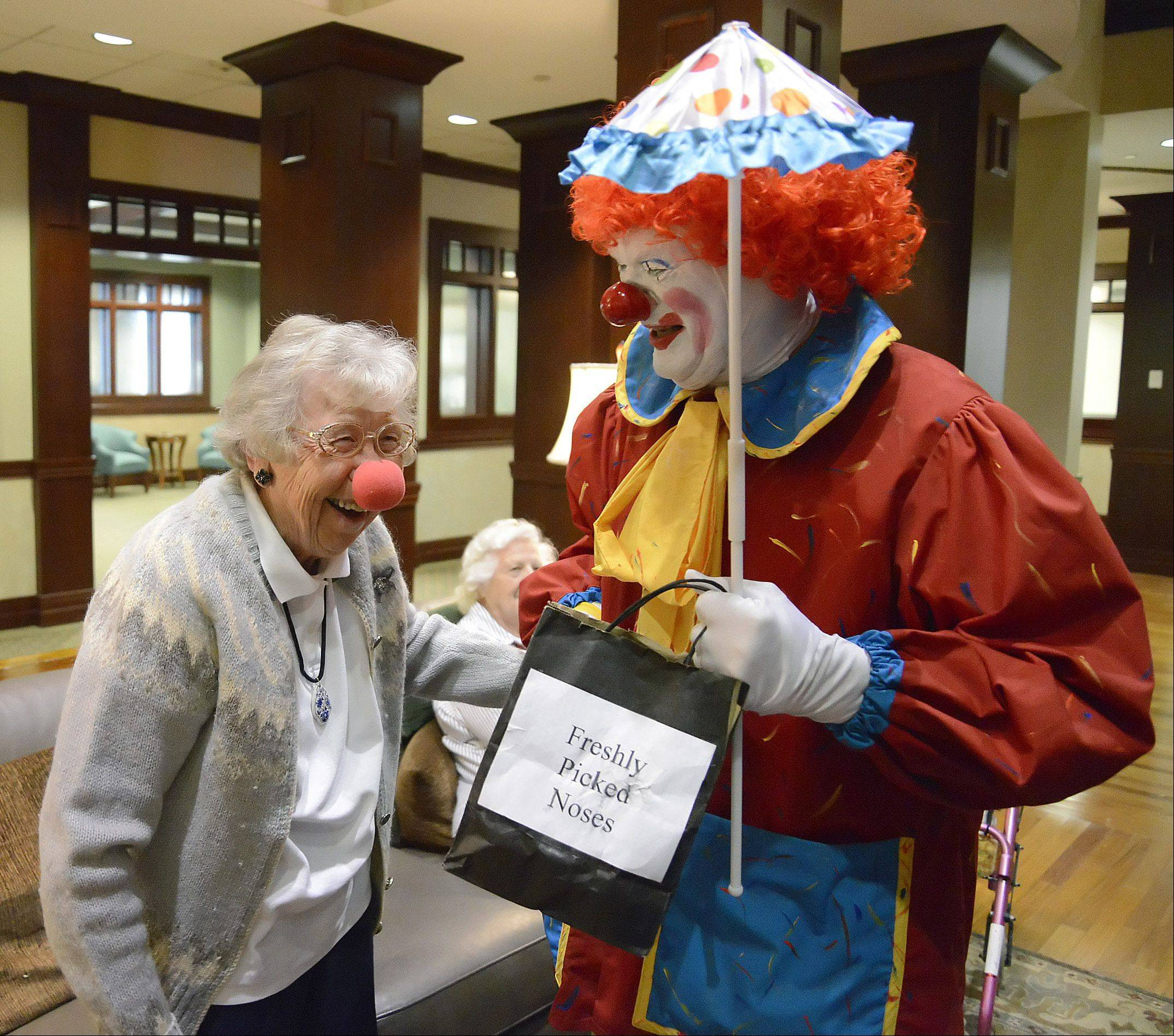 Inga Lind jokes with Polyester the clown after she received a foam nose, making her an honorary clown during a recent visit to The Holmstad in Batavia.