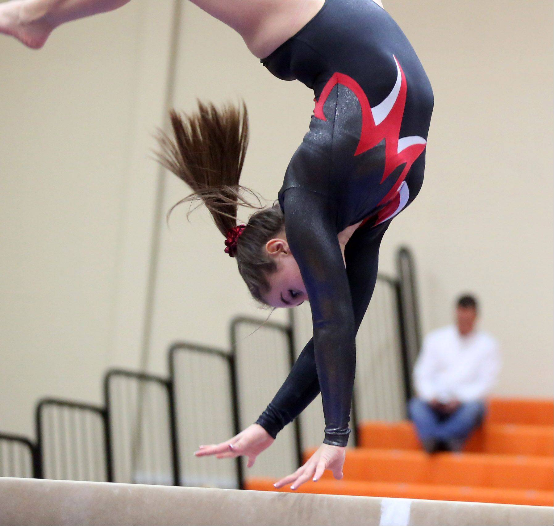 Mundelein's Taylor Kozaritz competes on the balance beam in a North Suburban Conference girls gymnastics meet on Friday at Libertyville.