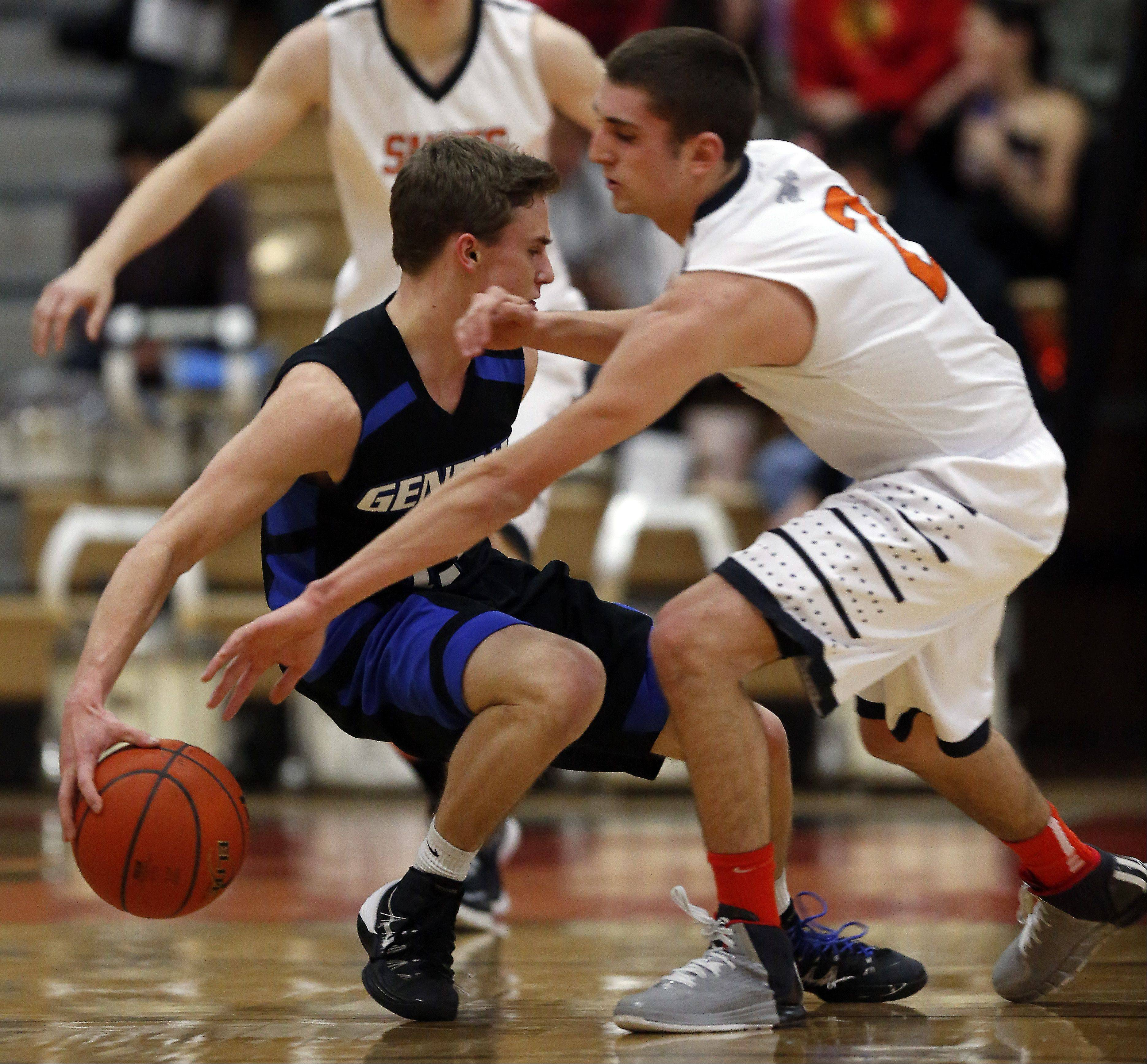 Geneva�s Cam Cook, 11, works the ball around his back and away from St. Charles East�s Dom Adduci, 2, during boys Basketball Saturday.