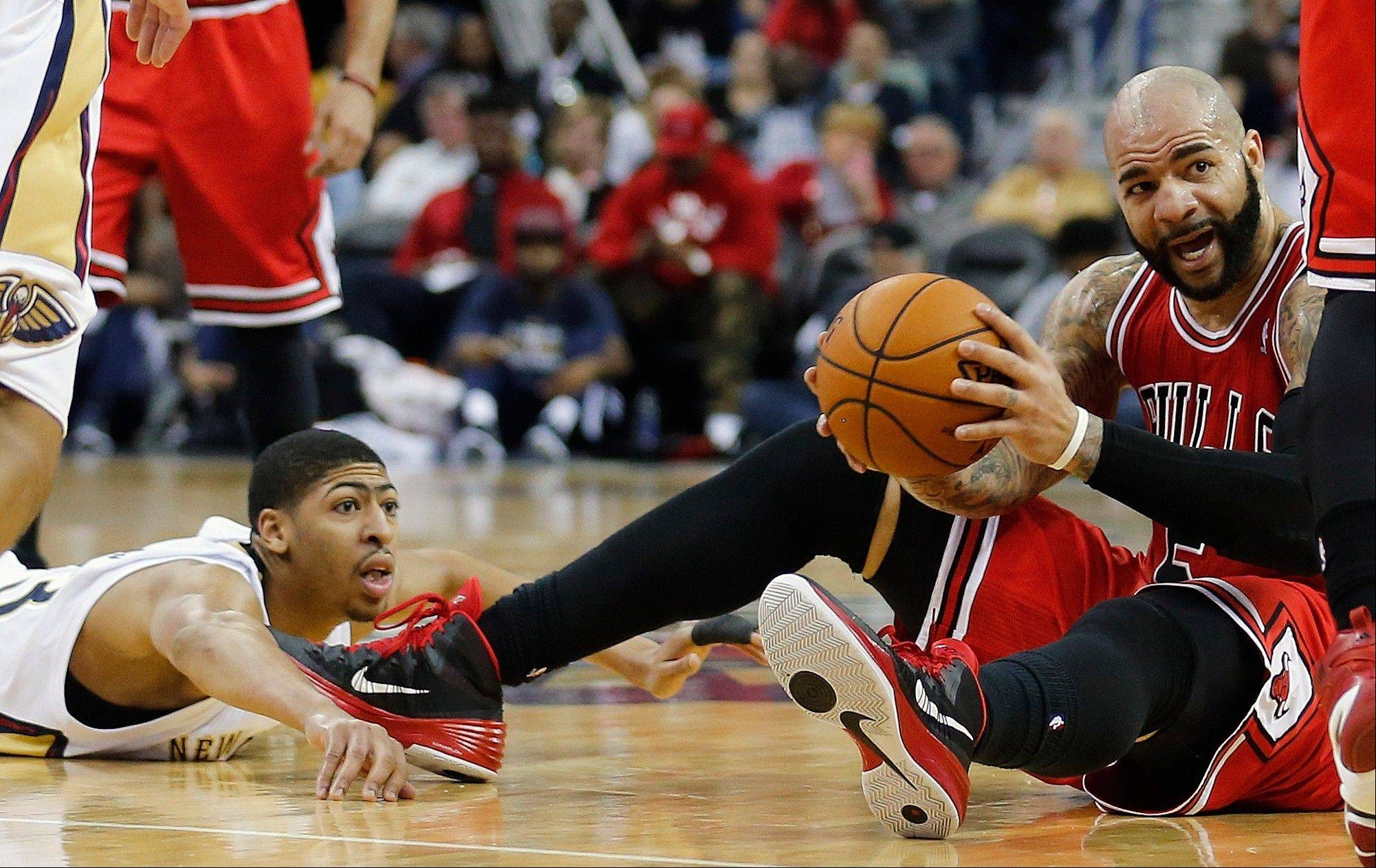 Bulls forward Carlos Boozer grabs a loose ball in front of New Orleans Pelicans forward Anthony Davis during the second half of an NBA basketball game in New Orleans, Saturday, Feb. 1, 2014. The Pelicans defeated the Bulls 88-79.