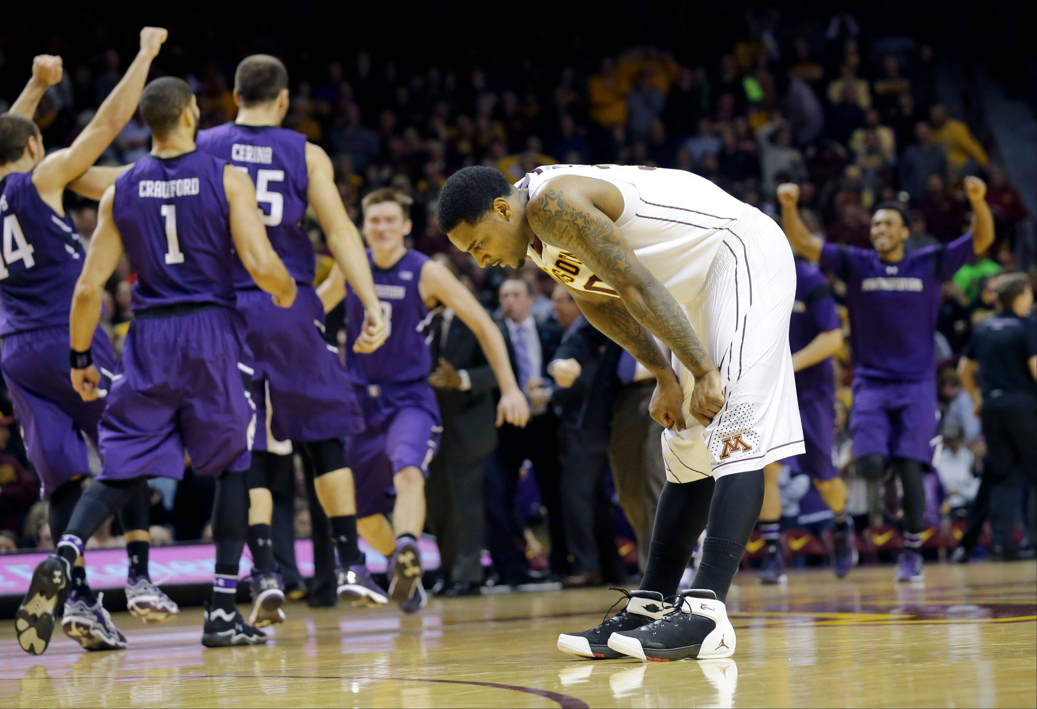 Minnesota guard Malik Smith reacts as Northwestern players celebrate after the Wildcatrs beat the Gophers 55-54 during an NCAA college basketball game in Minneapolis, Saturday, Feb. 1, 2014.