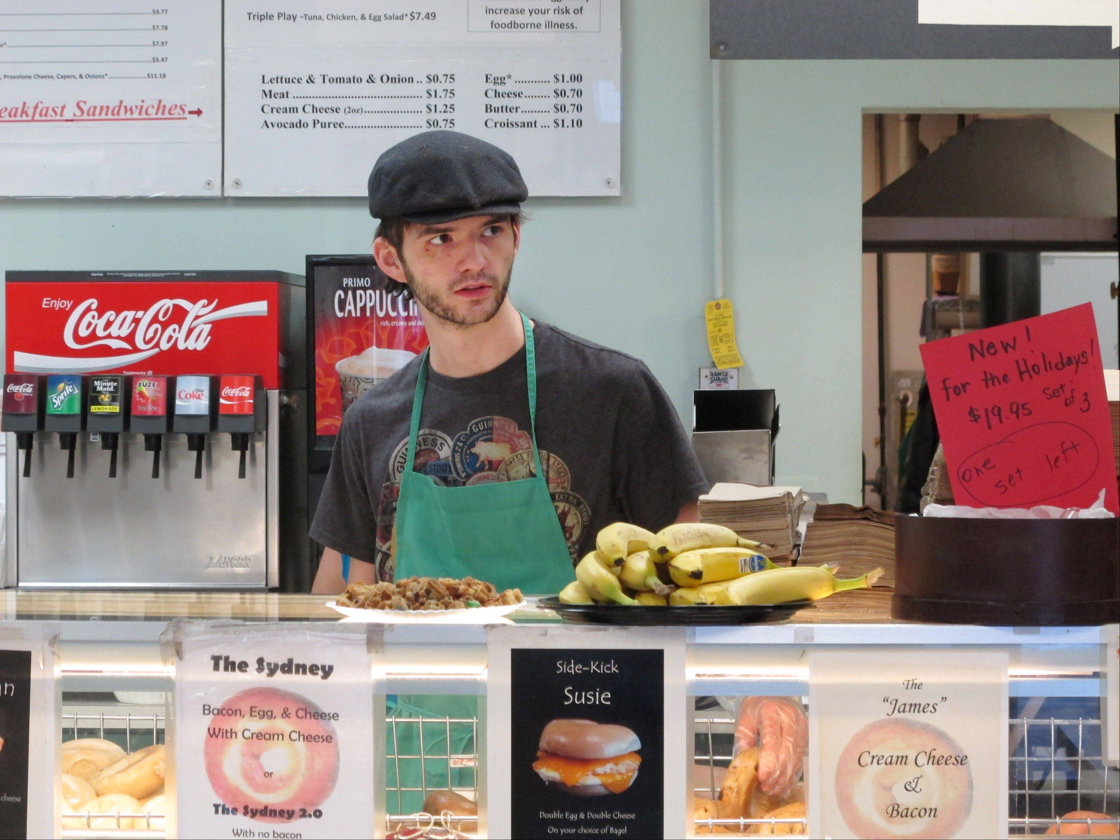 Neal Breen, 21, works Monday at the Ashburn Bagel & Sandwich Shop in Ashburn, Va. Breen, who quit college a year earlier with hopes of saving money to start his own business, is keenly aware that the wealth in the neighborhoods where he delivers breakfast sandwiches is, for now, beyond reach.