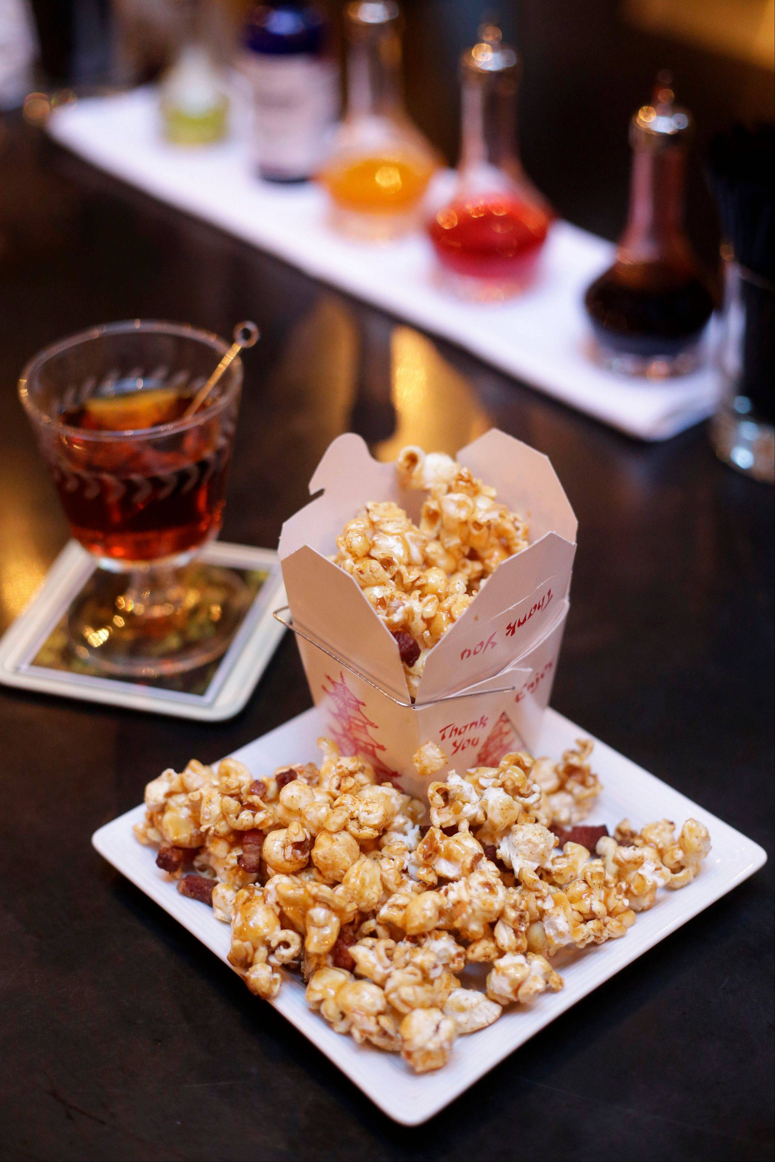 "A plate of bacon popcorn, front, sits on a bar next to a cocktail called the ""Model T"" at the backbar restaurant and bar in Somerville, Mass. Over the past several years, Somerville's eclectic Union Square neighborhood has become a drinking and dining destination."