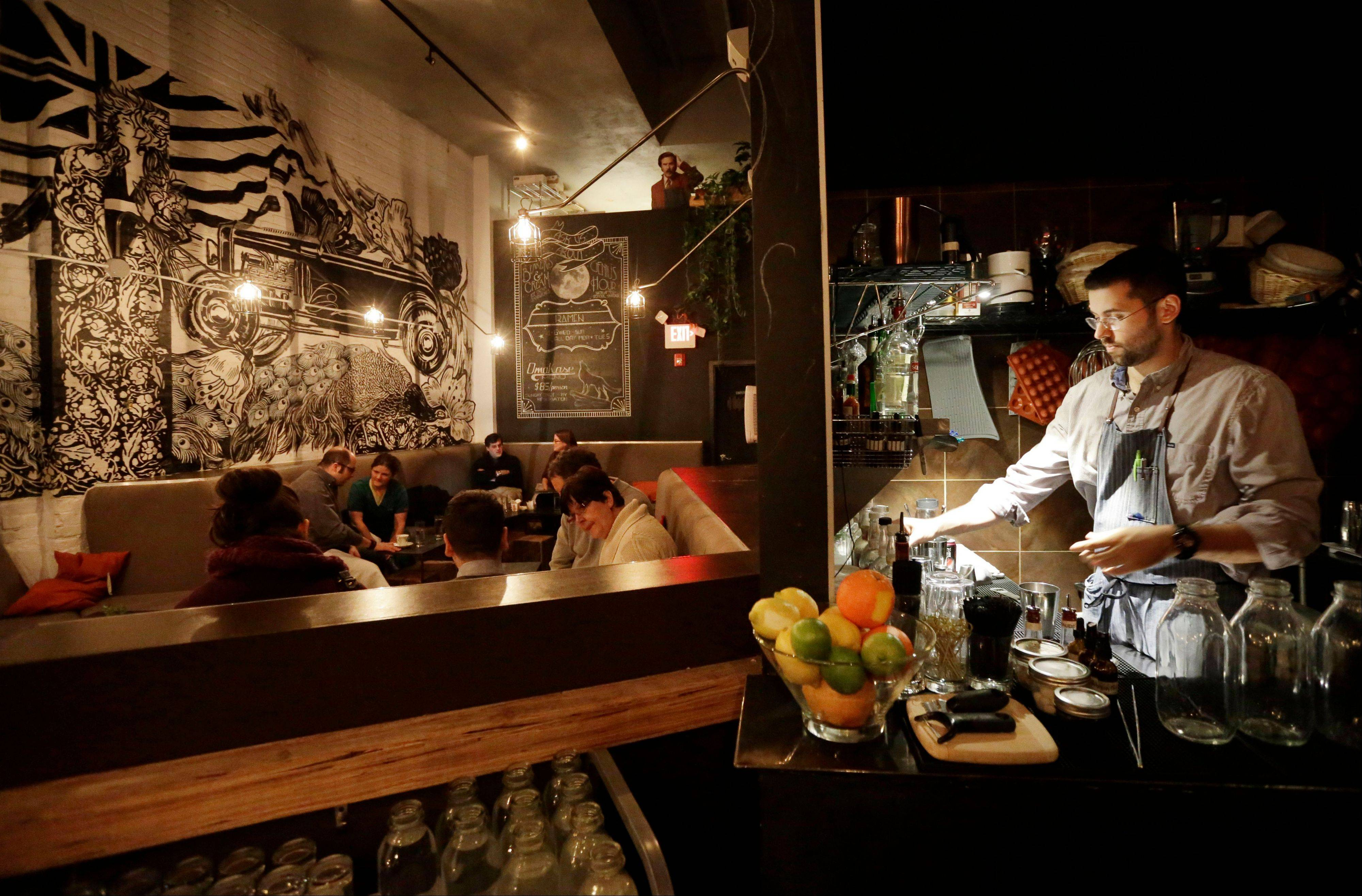 Bartender Joseph Cammarata, right, prepares drinks as patrons sit at tables at the backbar restaurant and bar in Somerville, Mass.