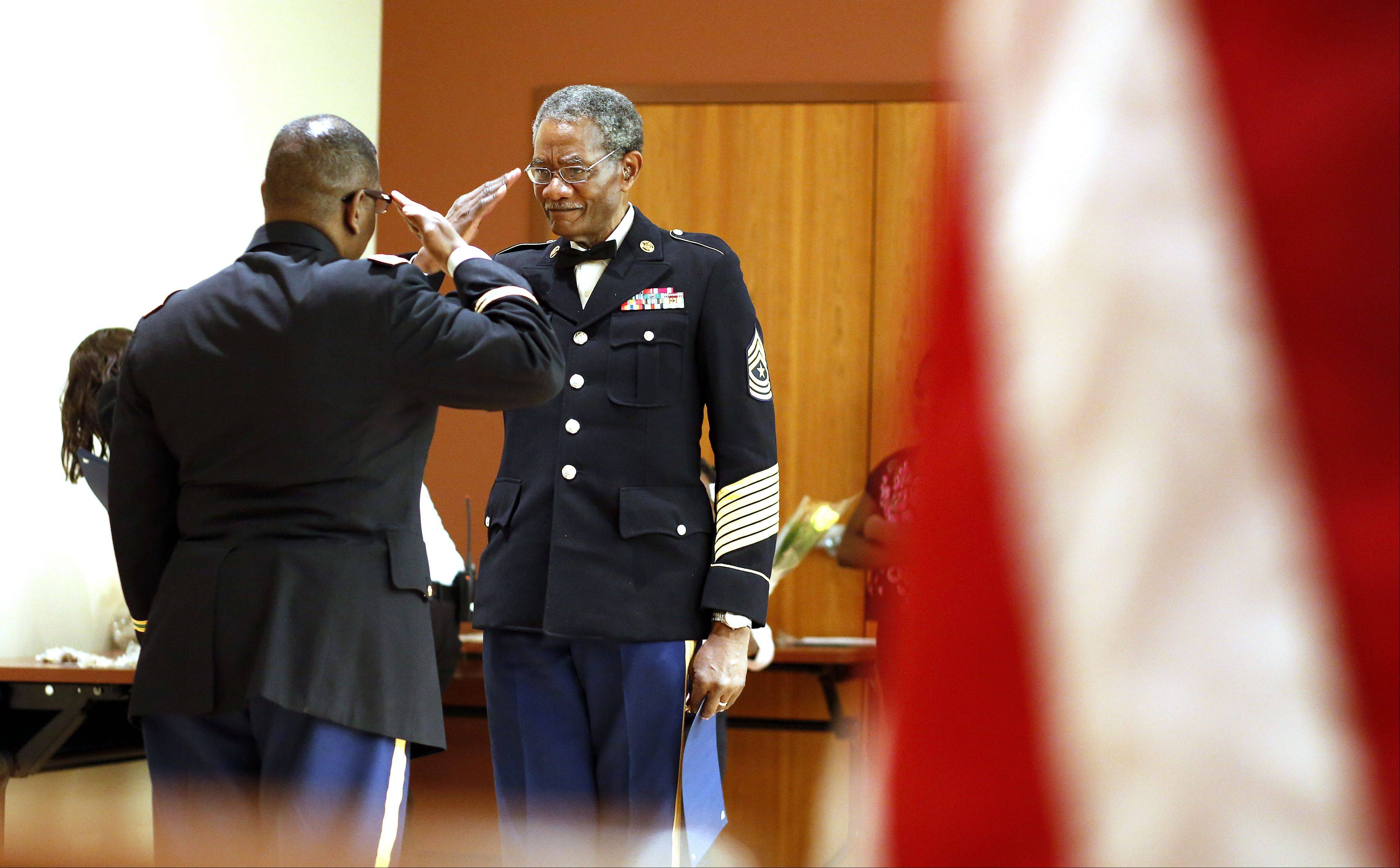 Retired Sgt. Maj. Rubert Carr of Elgin, right, salutes emcee Col. W.E. Scott, left, during the ninth annual Black History Family Festival on Saturday at the Gail Borden Public Library in Elgin. Carr retired in 1982.