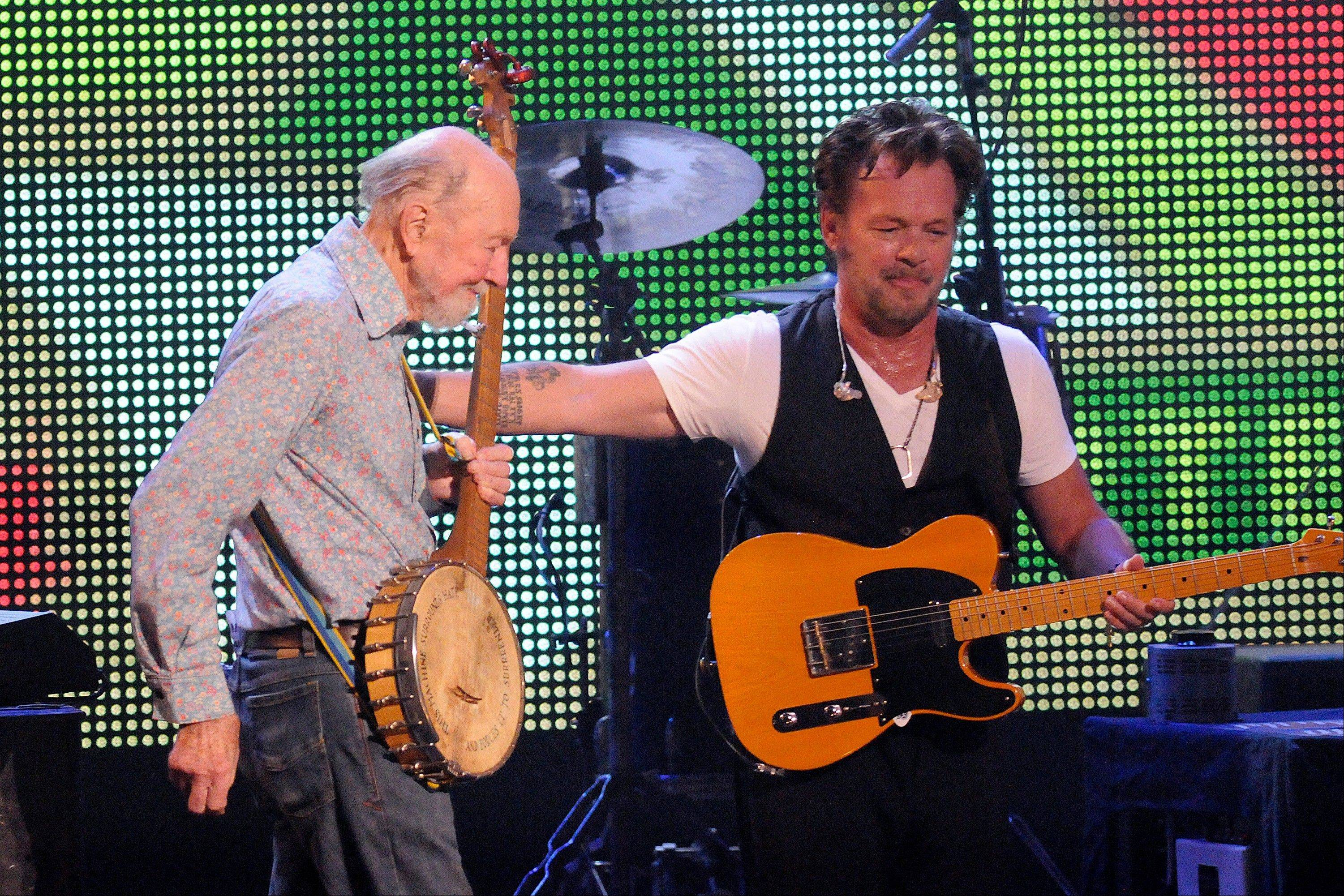 Pete Seeger, left, is welcomed on stage by John Mellencamp during the Farm Aid 2013 concert at Saratoga Performing Arts Center in Saratoga Springs, N.Y.