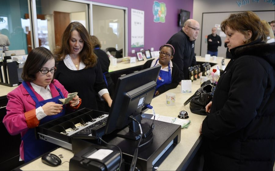 Megan Niklas of Naperville, left, and volunteer Kim Matz, center, assist Hoffman Estates Village Clerk Bev Romanoff at the checkout during the grand opening of Hugs & Mugs Gift Shop and Cafe, a storefront offering keepsake mugs and other gift items designed by adults with Down syndrome to support GiGi's Playhouse.
