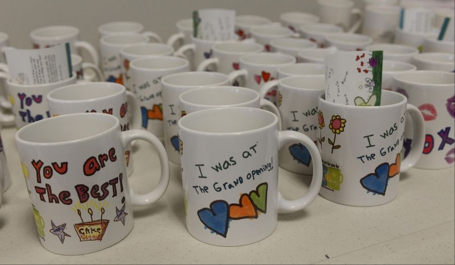 Dozens of mugs line a countertop during the grand opening of Hugs & Mugs Gift Shop and Cafe, a storefront offering keepsake mugs and other gift items designed by adults with Down syndrome to support GiGi's Playhouse.