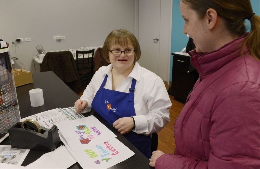 Christine Maxwell, left, shows Erin Gunsteen of Schaumburg how she applies her hand-drawn designs to mugs during the grand opening of Hugs & Mugs Gift Shop and Cafe, a storefront offering keepsake mugs and other gift items designed by adults with Down syndrome to support GiGi's Playhouse.