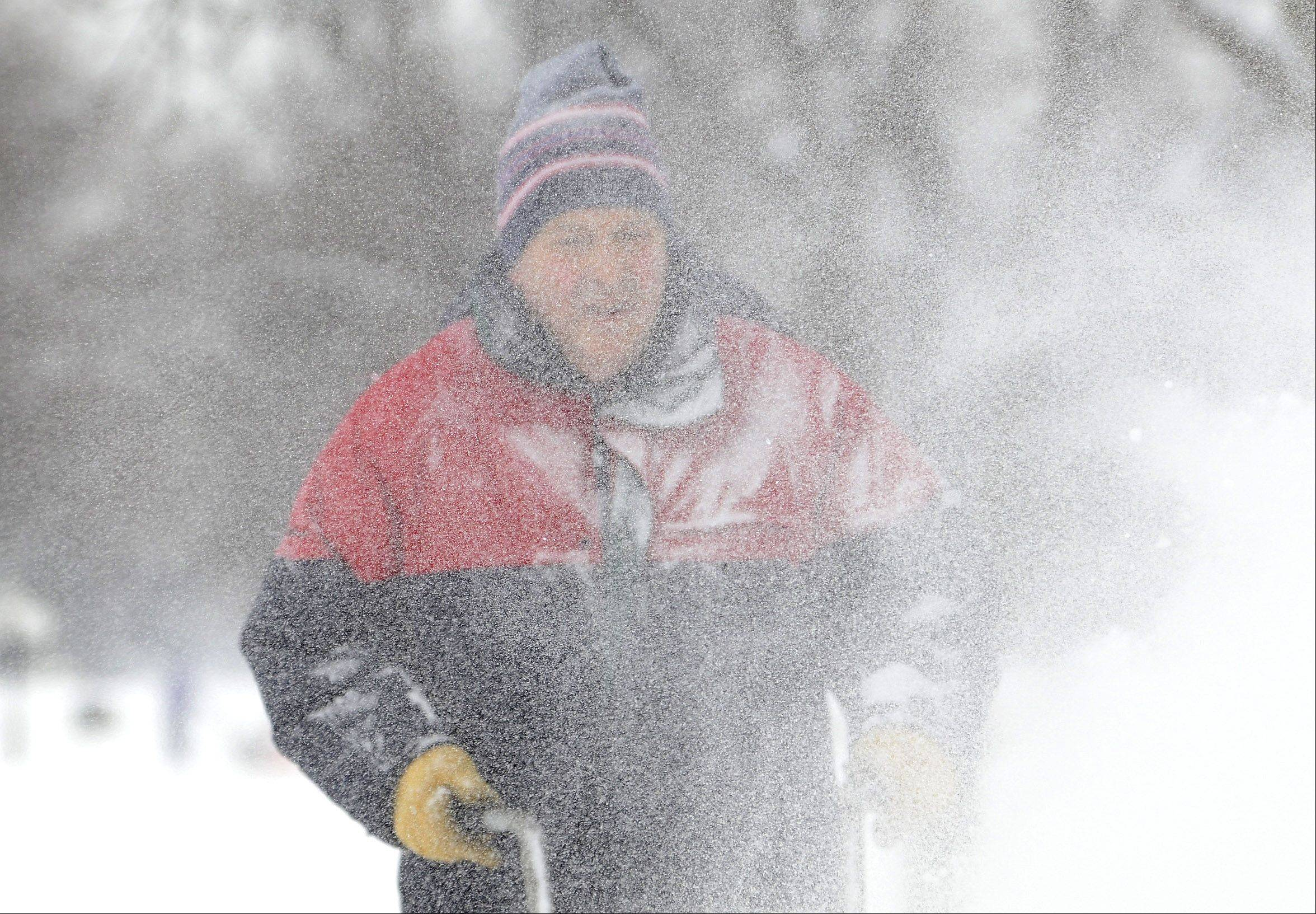 Bernie Wagner is covered in a veil of snow as he clears the sidewalk in front of his home on Knollwood Drive in Schaumburg Saturday morning.