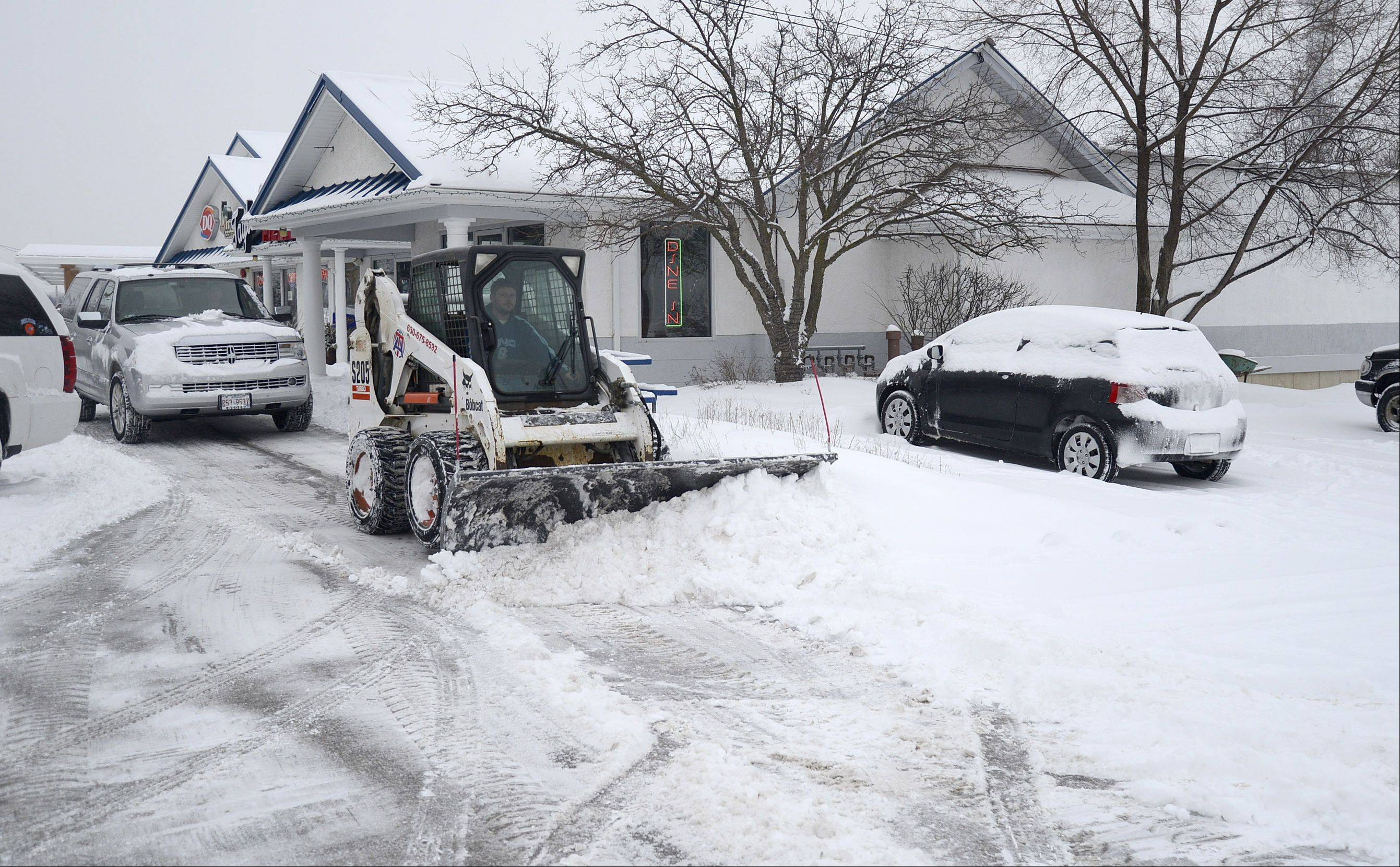 Travis Crabtree with T and A Contractors out of Maple Park clears snow from the parking lot of a business strip building in Wasco on Saturday morning. This was one of 10 properties he was in charge of plowing.