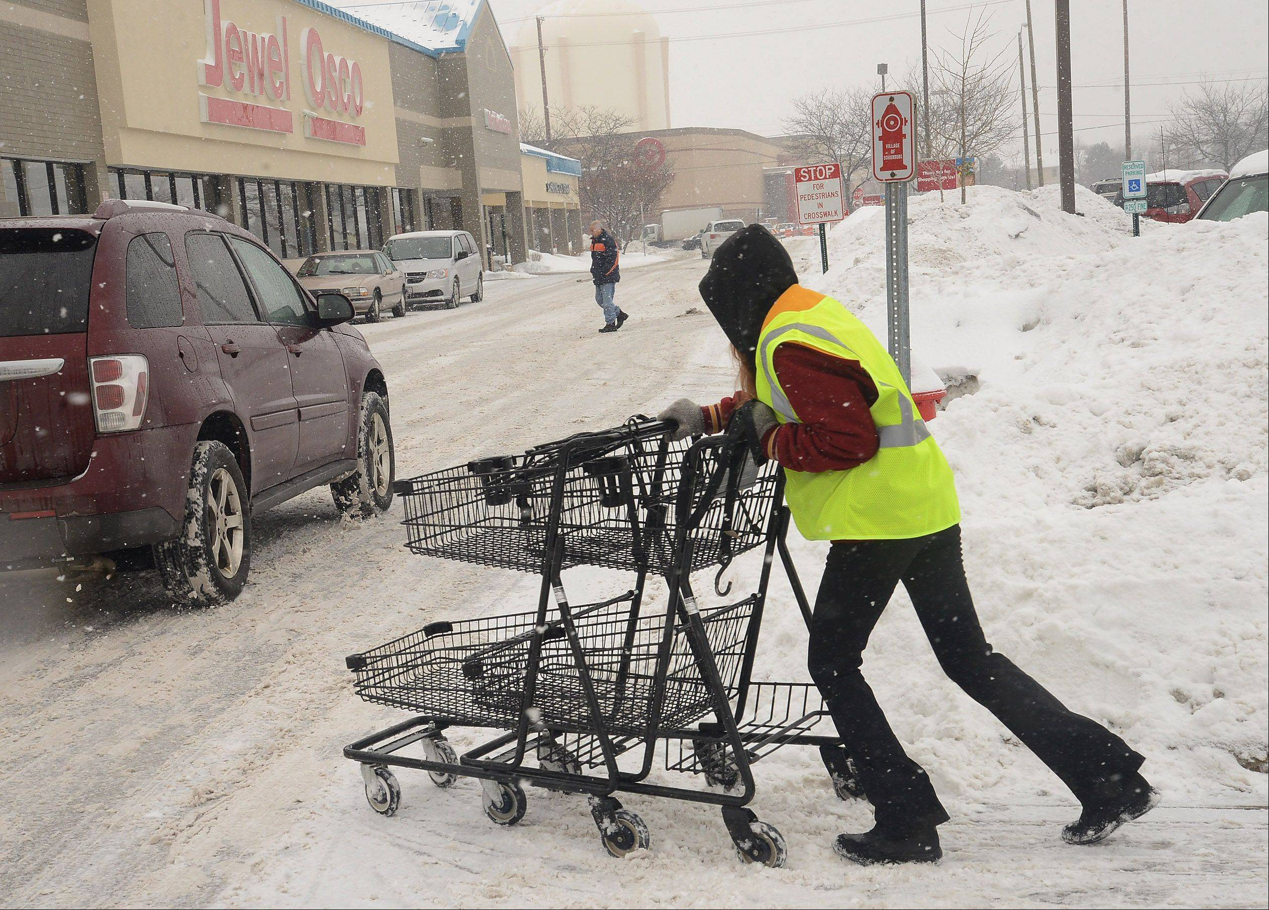 Becca Chapin retrieves some shopping carts at a Jewel Osco in Schaumburg Saturday.