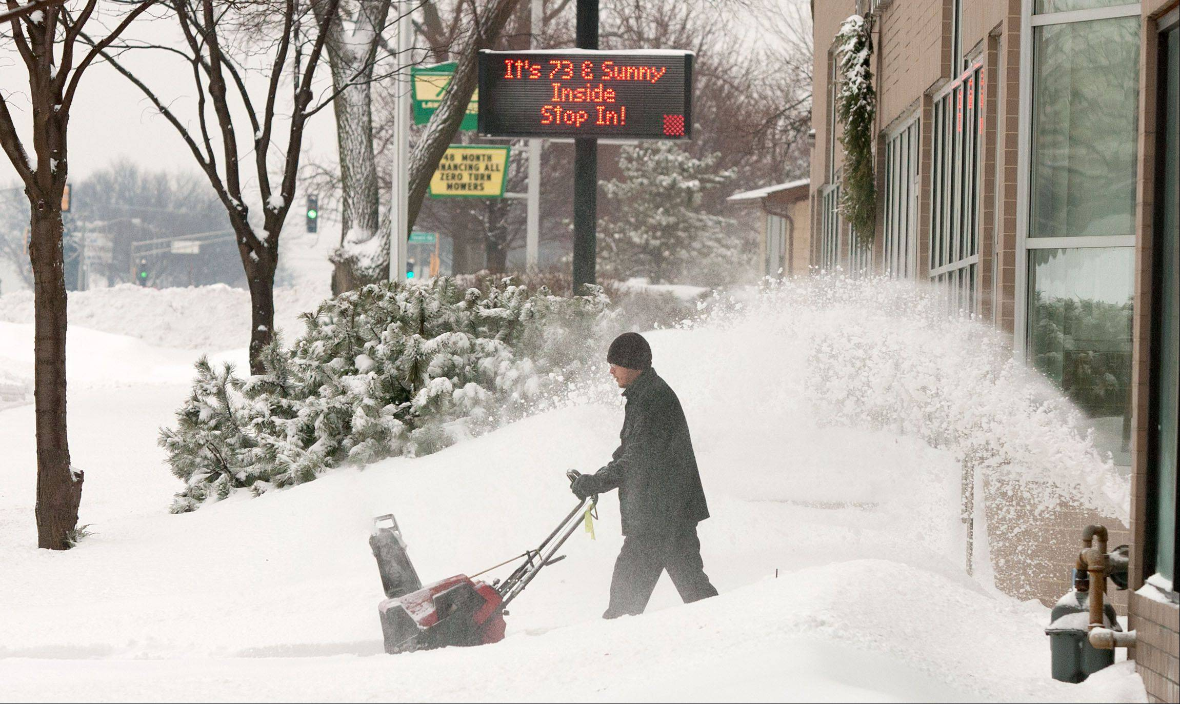 It may be 73 degrees inside the Heritage Harley Davidson Lisle dealership, but Javier Pena knows it is not that temperature outside, as he plows another round of snow.