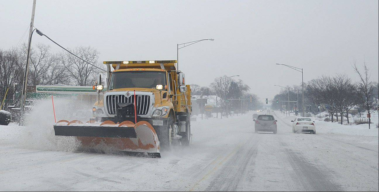 A snowplow heads west on Route 64 approaching Randall Rd in St. Charles on Saturday morning.