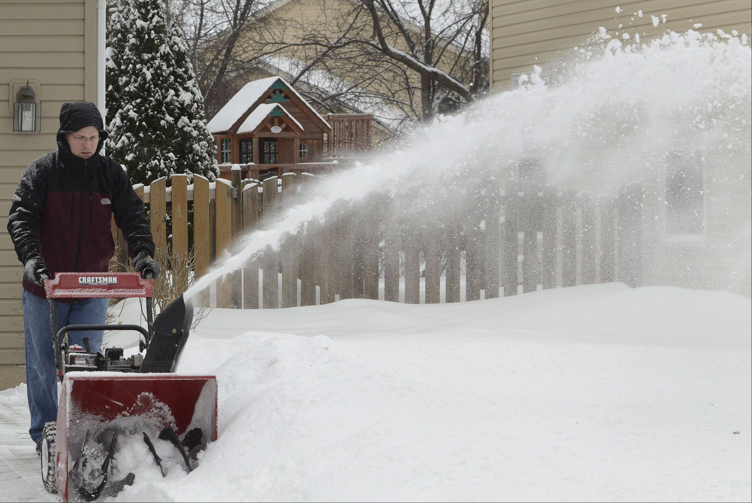 Bill Burgraff clears his driveway Saturday on Kingsbury Drive in Schaumburg.