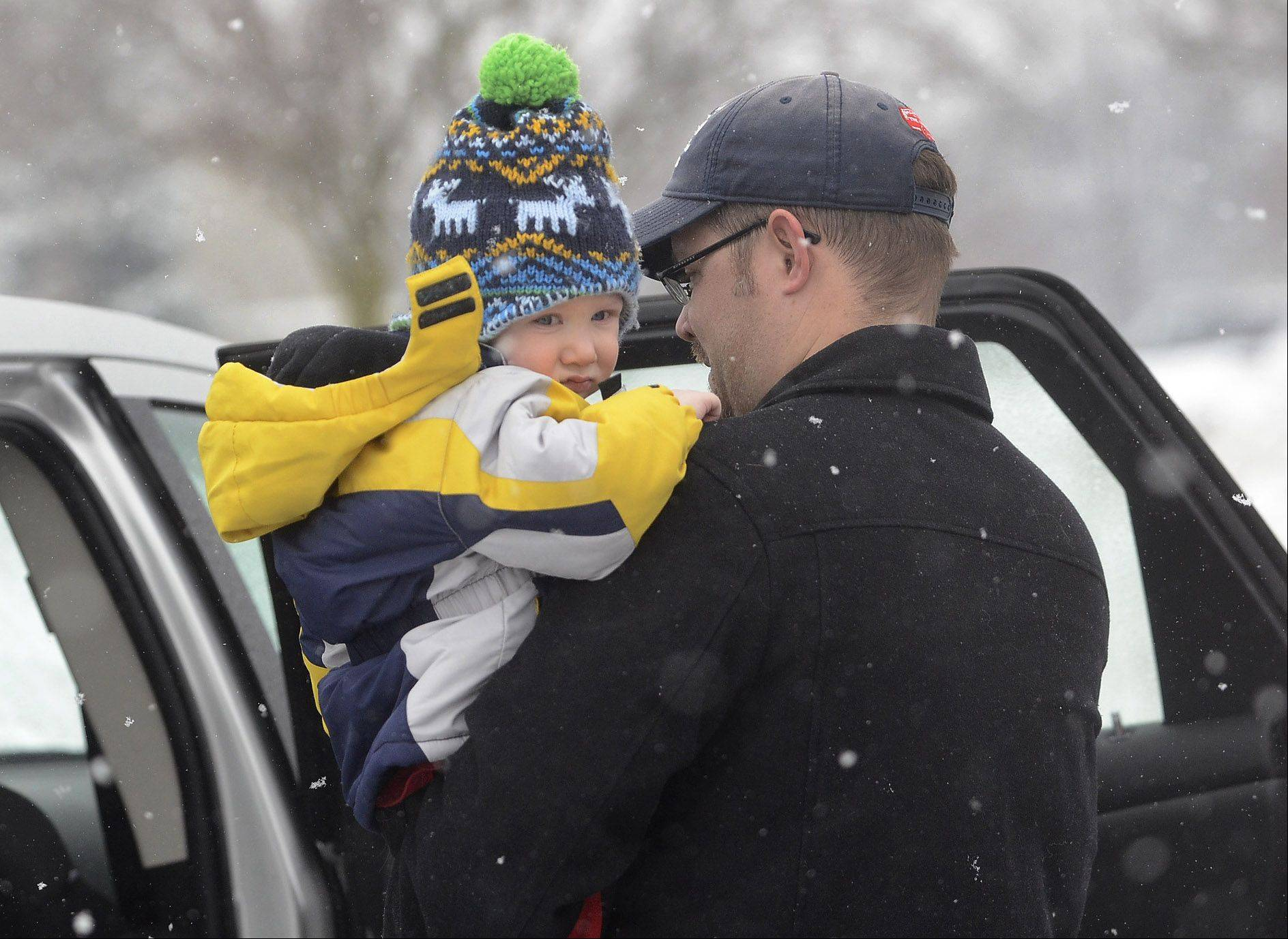 Jon Feucht of Schaumburg packs his son Zander into his vehicle after the 2-year-old got his hair cut Saturday.