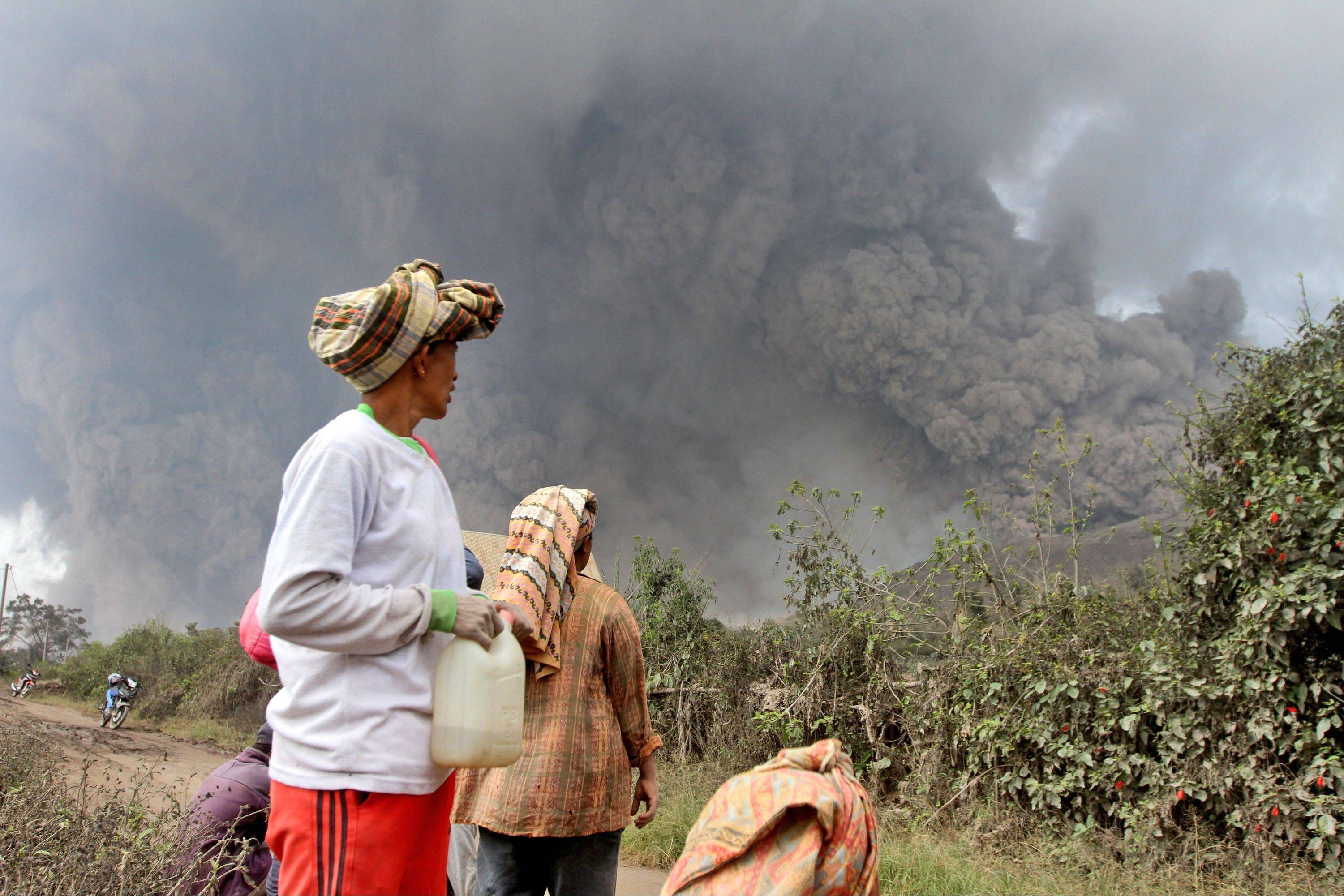 Villagers watch Saturday as Mount Sinabung releases pyroclastic flows during an eruption in Namantaran, North Sumatra, Indonesia.
