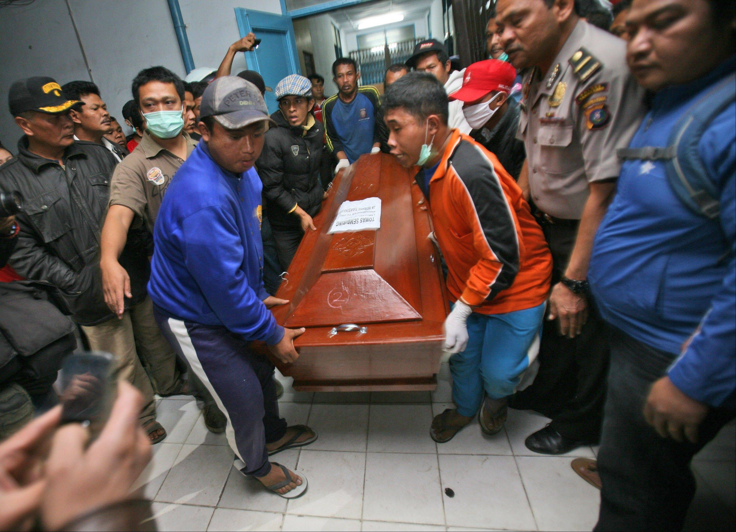 Relatives carry a coffin Saturday containing the body a victim of the eruption of Mount Sinabung, at a hospital in Kabanjahe, North Sumatra, Indonesia.