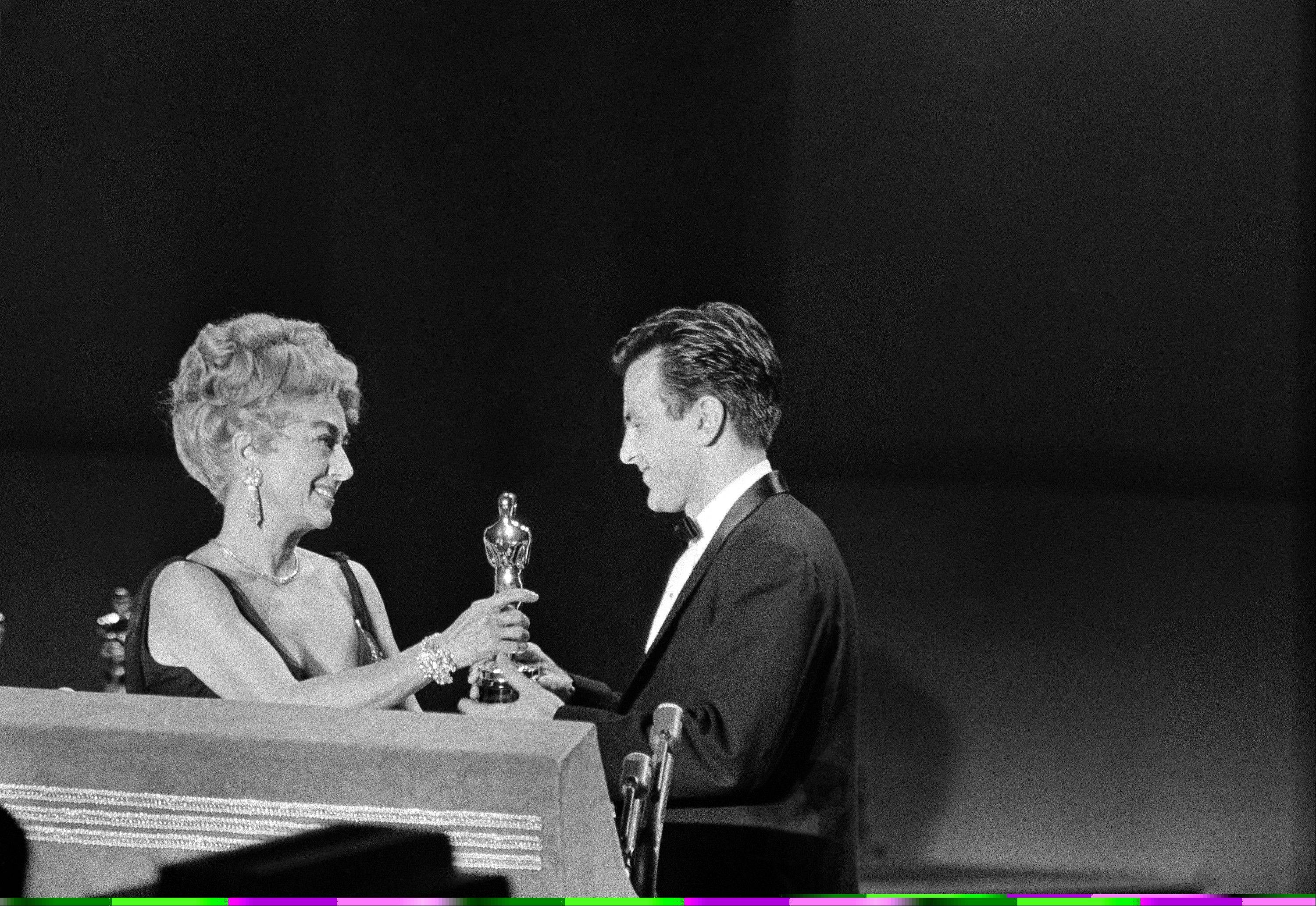 "In this April 9, 1962 file picture Joan Crawford, acting as presenter for the Academy of Motion Picture Arts and Sciences, presents an Oscar to Maximilian Schell on the stage at Santa Monica, Calif., April 9, 1962, after he was named as best actor of the year for his performance in ""Judgment at Nuremberg."" The Austrian actor, who won the best actor Oscar in the early 1960s, has died. He was 83. Schell's agent Patricia Baumbauer said Saturday Feb. 1, that Schell died overnight at a hospital in Innsbruck following a ""sudden and serious illness,"" the Austria Press Agency reported."