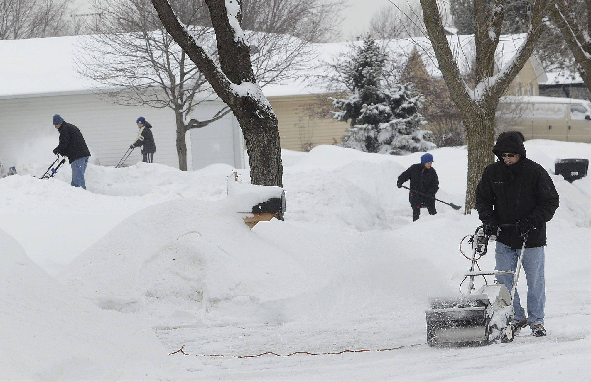 Barry Rothblum, right, joins forces with his next-door neighbors Carol and Robert Chubb on Islington Lane in Schaumburg, as they dig out Saturday morning.
