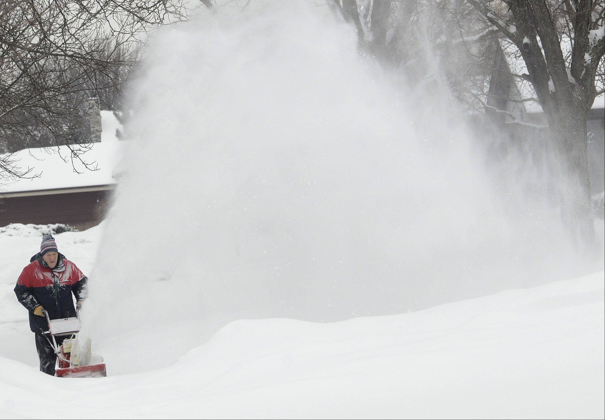Bernie Wagner of Knollwood Drive in Schaumburg shoots a plume of snow from his snowblower as he digs out from Saturday's snowfall.