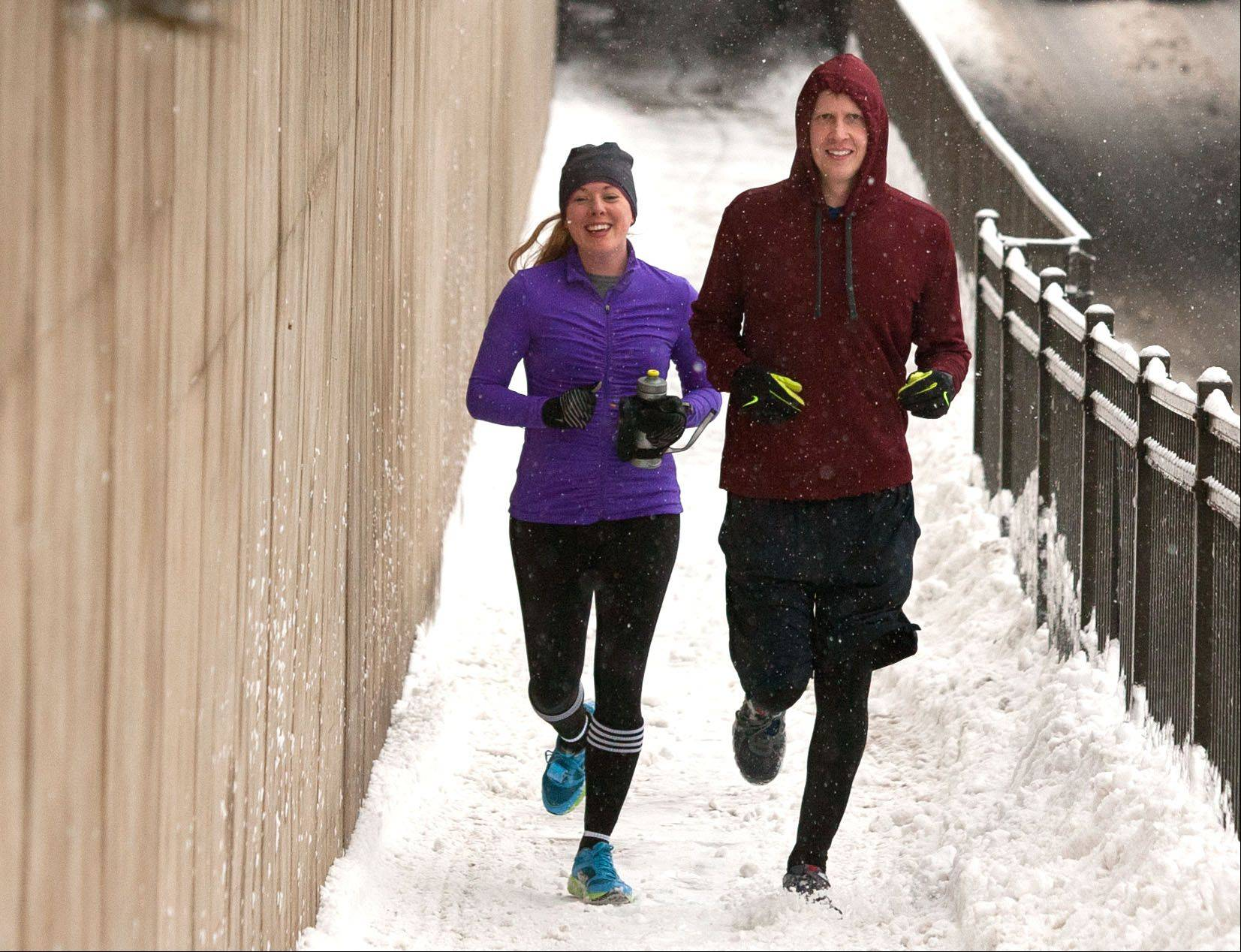 Teresa Nydegger, left, of Naperville and Shawn Pajor, right, of Palatine don't mind the snow as they run through downtown Naperville.