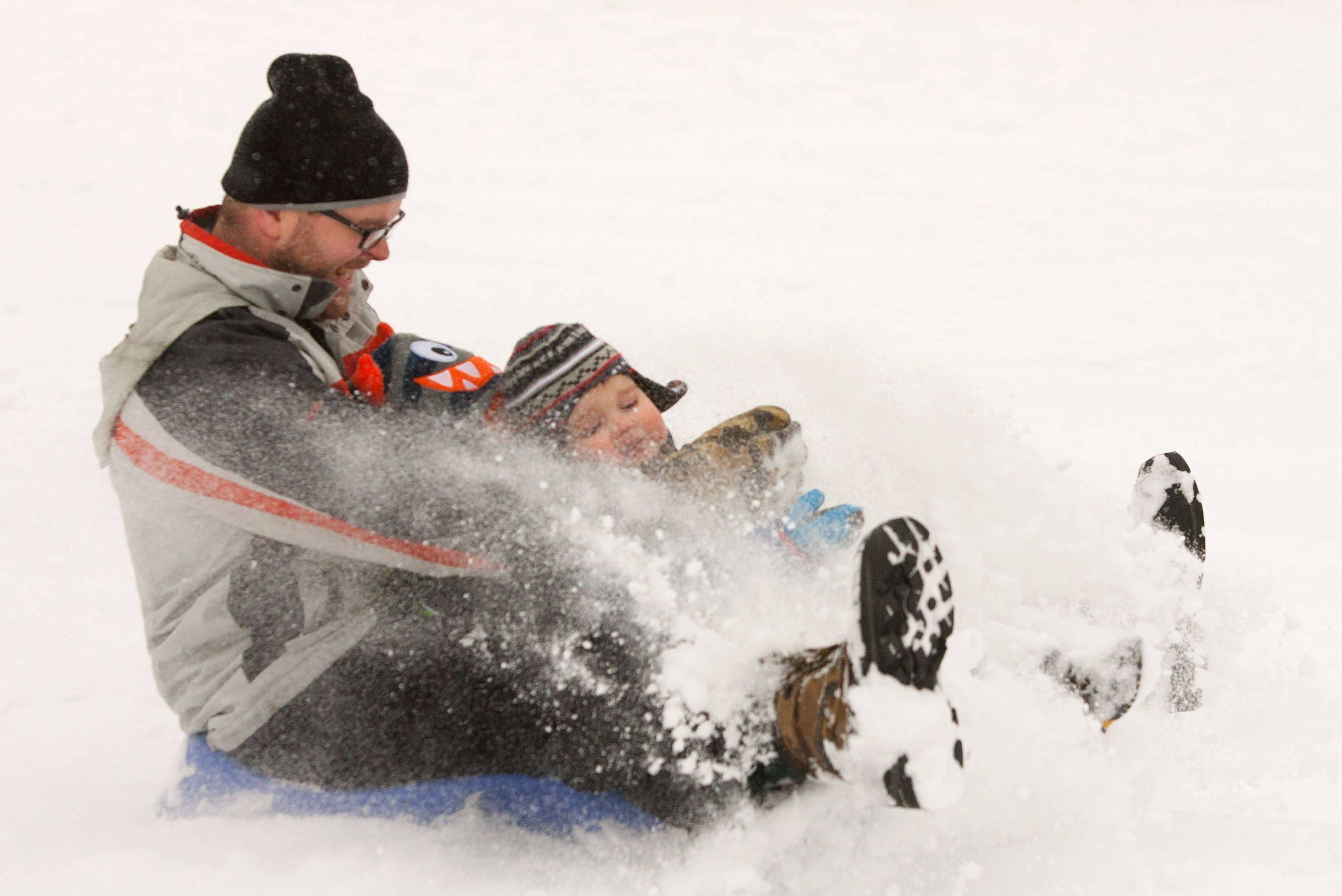 Jeff Leach of Aurora slides down Rotary Hill in Naperville with his sons Caleb, 3, and Noah, 2, as another round of snow makes its way through the suburbs.