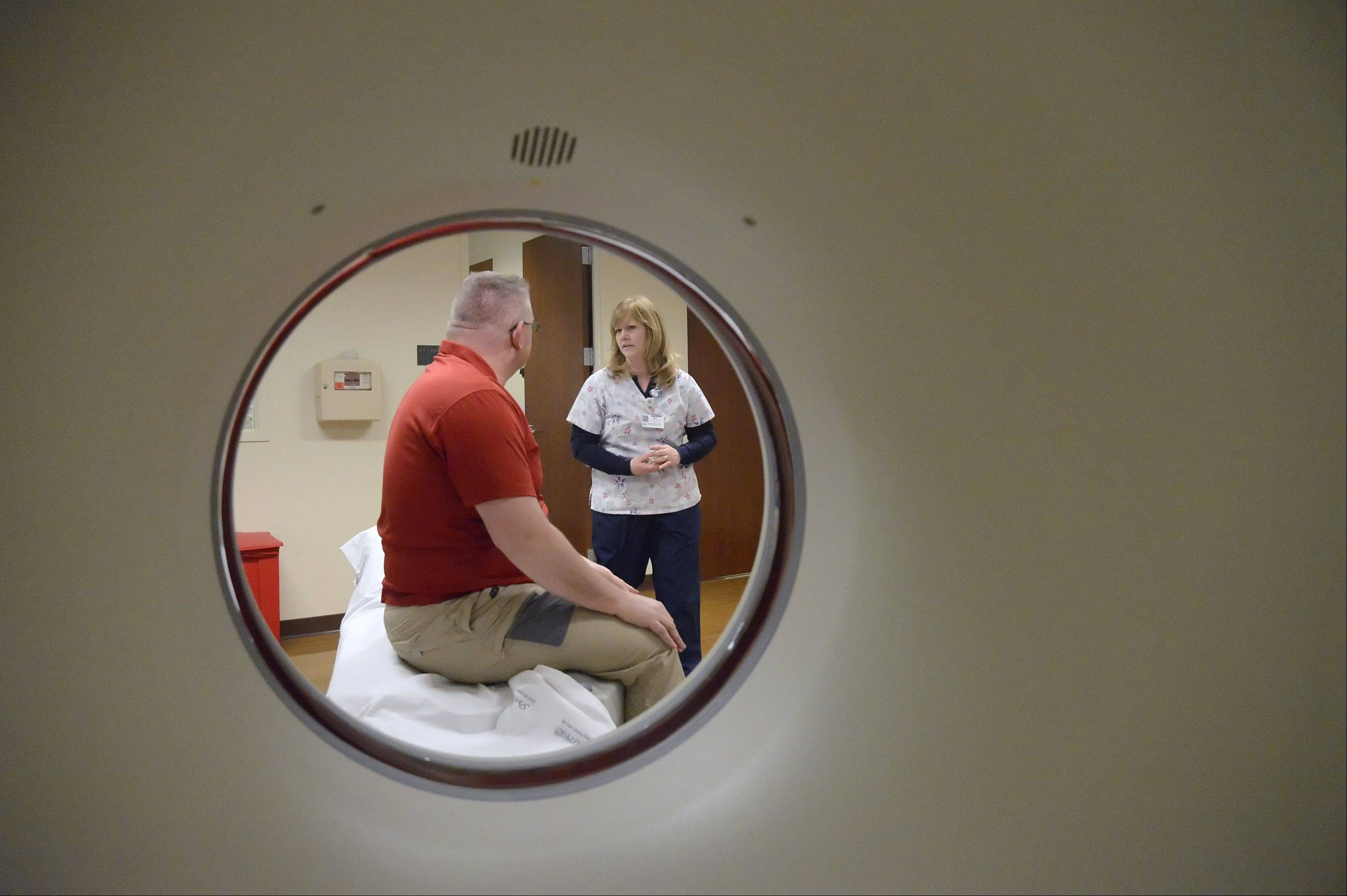 CT Technologist Kat Kearney chats with Kane County Coroner Rob Russell after his heart CT scan Advocate Sherman Hospital's outpatient center in South Elgin. Russell was in the scanner less than 30 seconds.