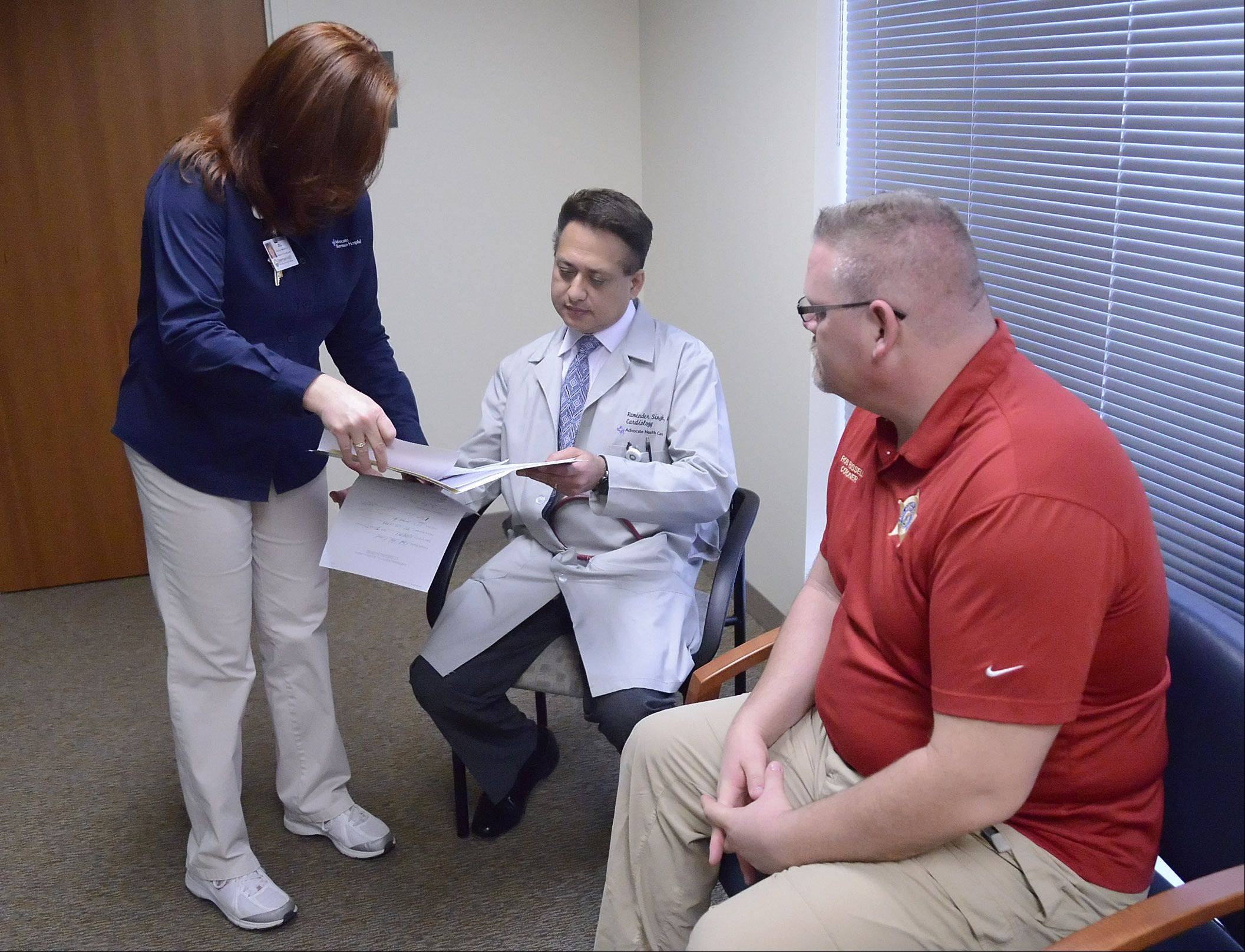 Sherman Health Community Wellness Coordinator Jill League delivers immediate test results to cardiologist Dr. Raminder Singh to discuss with Kane County Coroner Rob Russell. The screening takes about an hour.