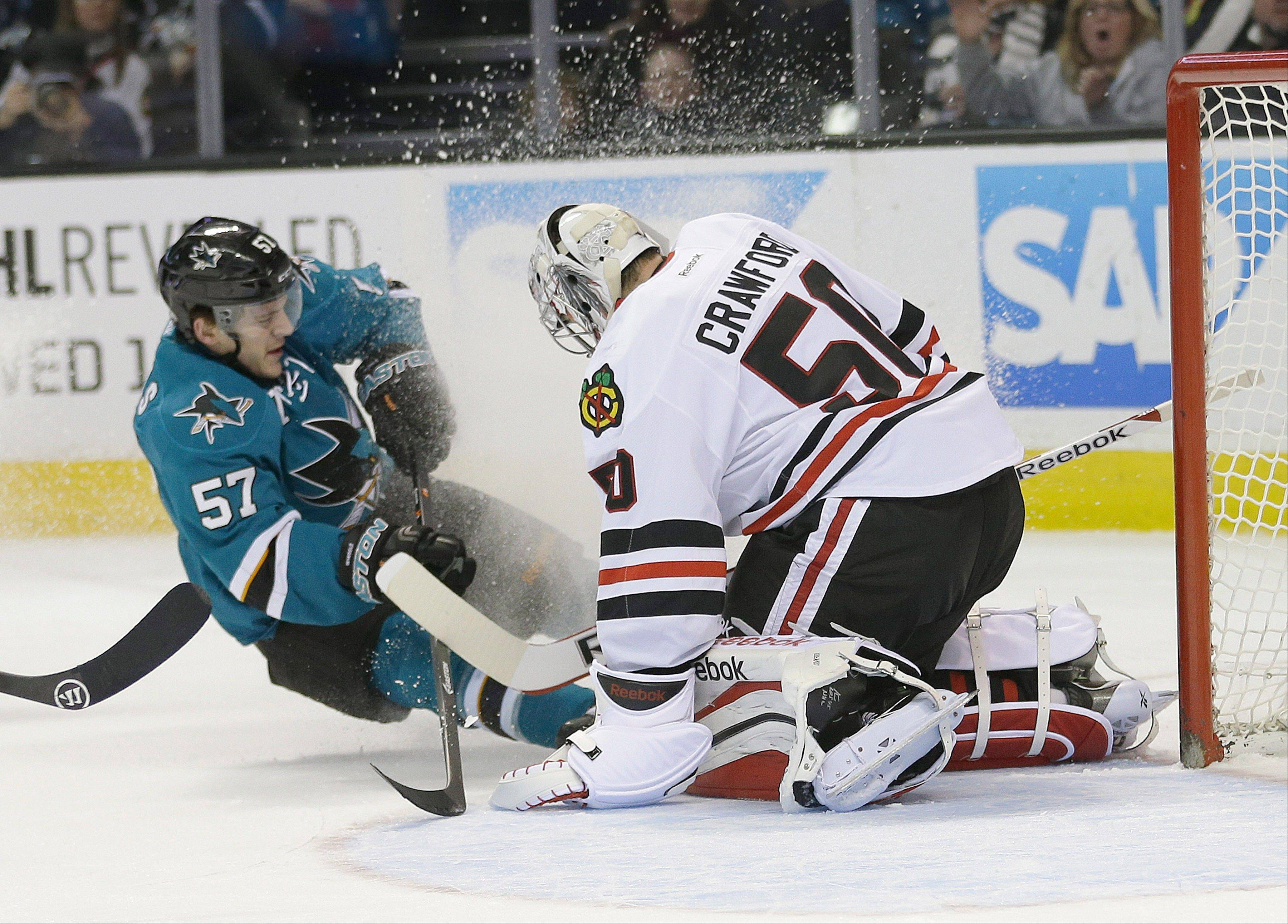 Hawks goalie Corey Crawford blocks a shot from the Sharks' Tommy Wingels during the first period Saturday in San Jose.