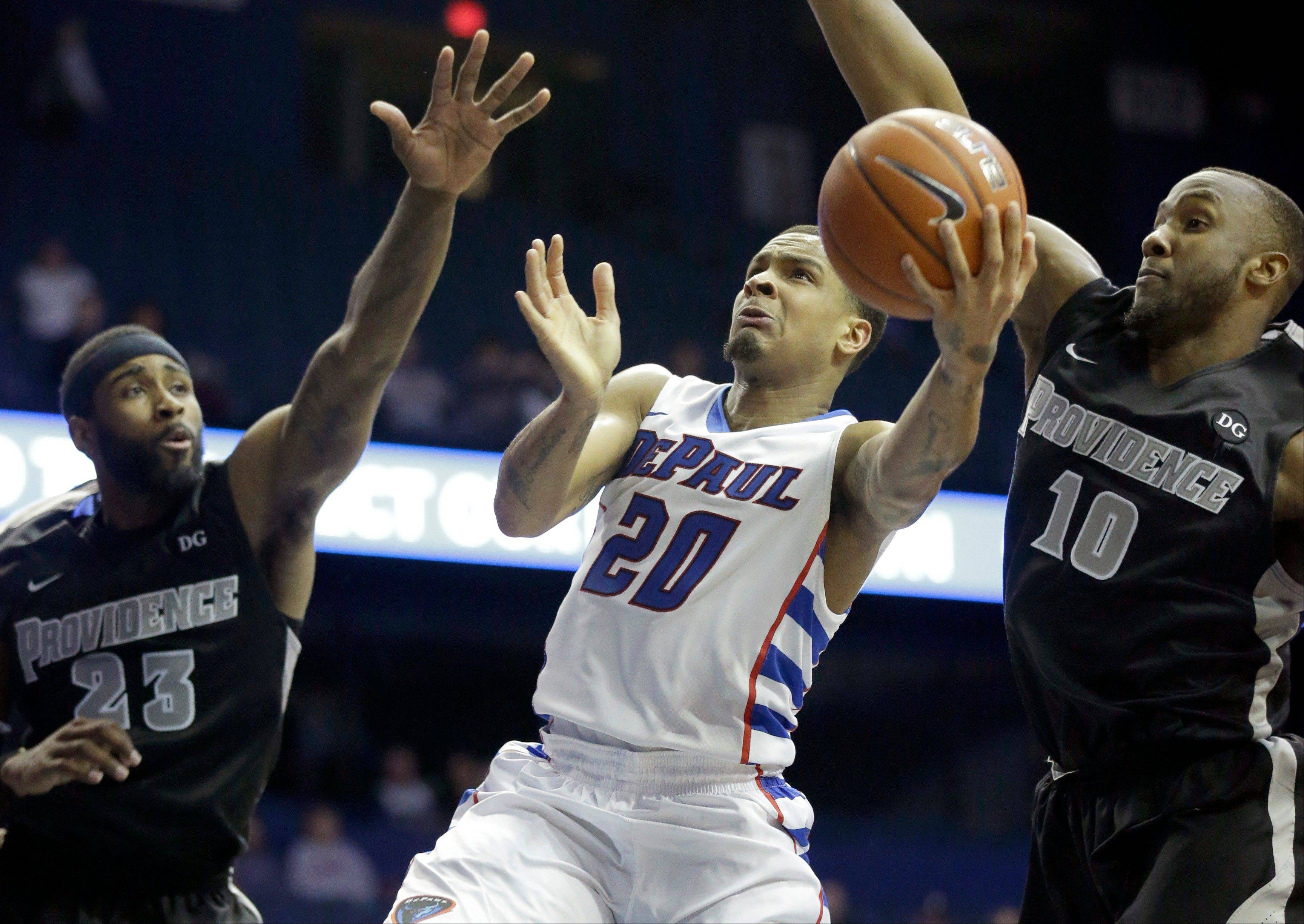DePaul guard Brandon Young (20) drives to the basket against Providence forward LaDontae Henton (23) and Kadeem Batts (10) during the second half of an NCAA college basketball game in Rosemont, Ill., on Saturday, Feb. 1, 2014. Providence won 77-72.