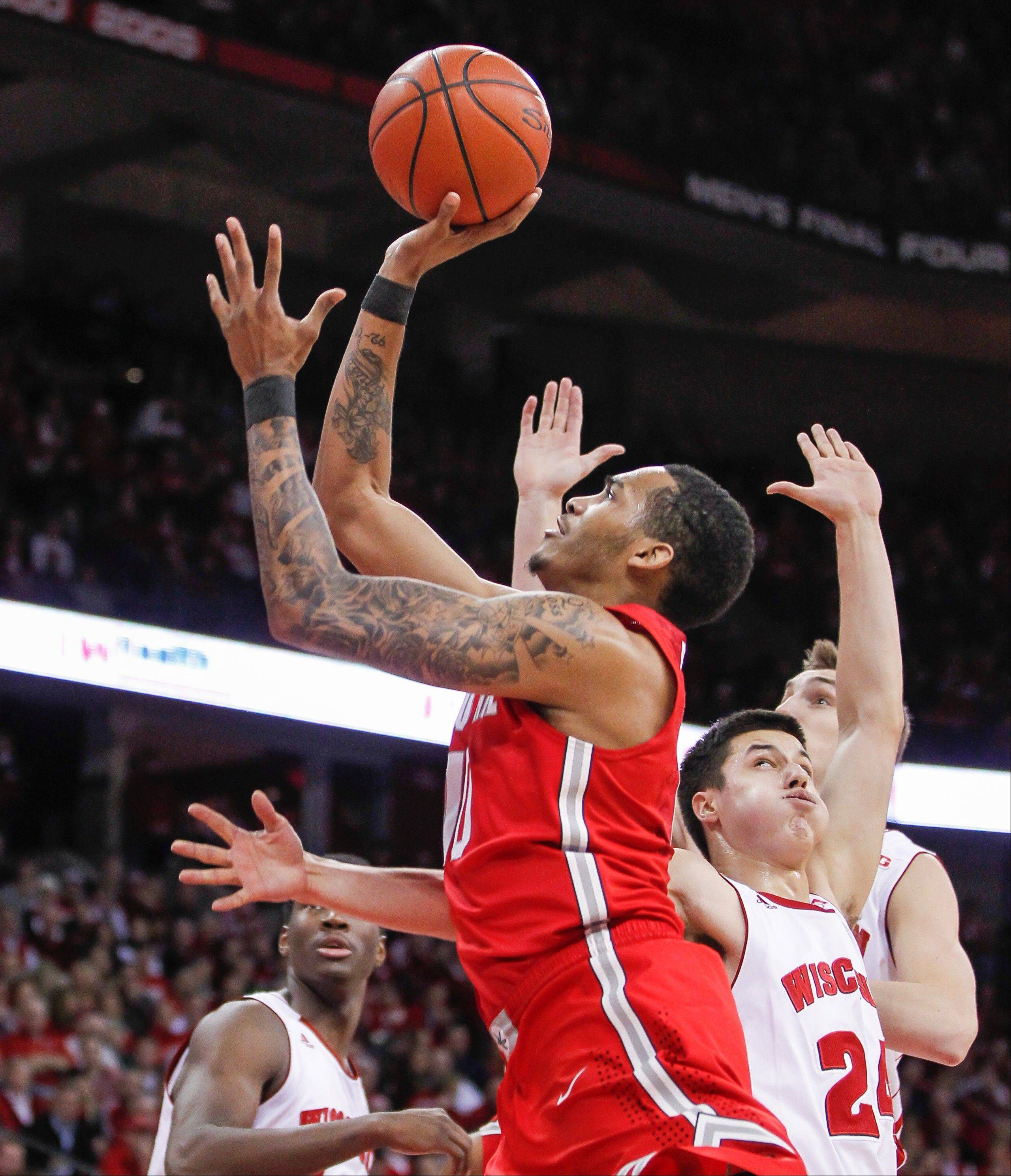 Ohio State's LaQuinton Ross shoots past Wisconsin's Bronson Koenig (24) during the first half of an NCAA college basketball game Saturday, Feb. 1, 2014, in Madison, Wis. Ross had a team-high 13 points in Ohio State's 59-58 win.