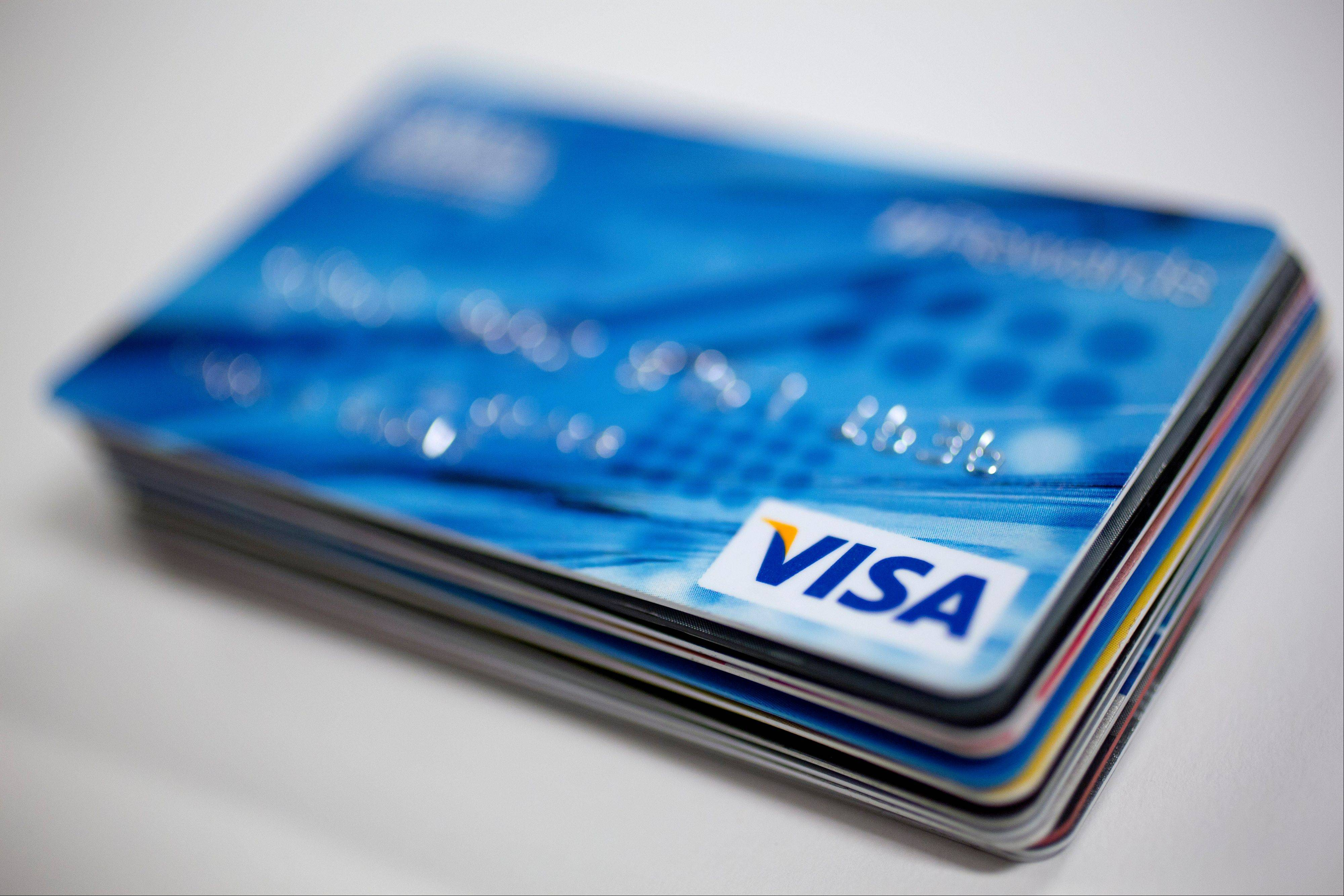A Visa Inc. credit card sits on top of credit and debit cards arranged for a photograph in Washington, D.C., U.S., on Wednesday, Jan. 29, 2014.
