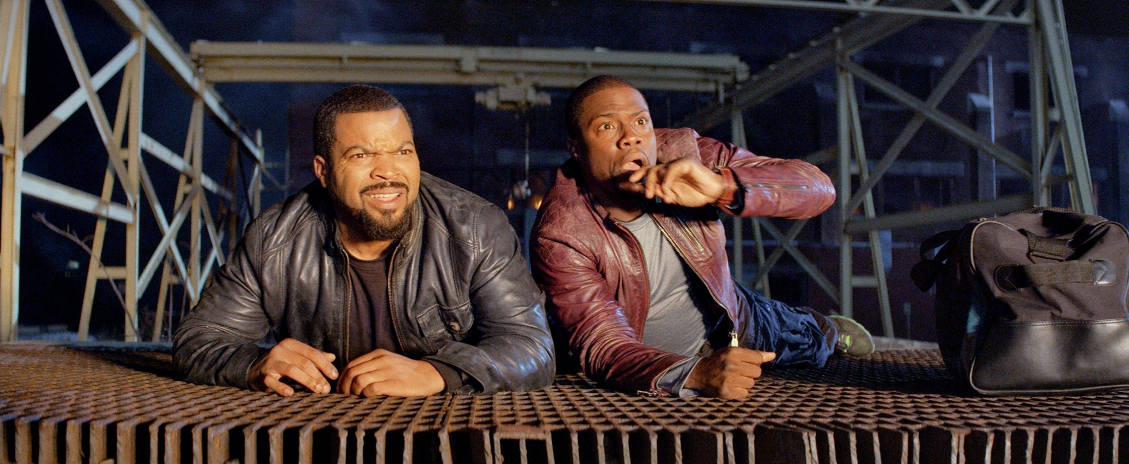 This image released by Universal Pictures shows Ice Cube, left, and Kevin Hart in a scene from the film, �Ride Along.� The film kept its hold on the top spot at the box office with a $12.3 million haul.