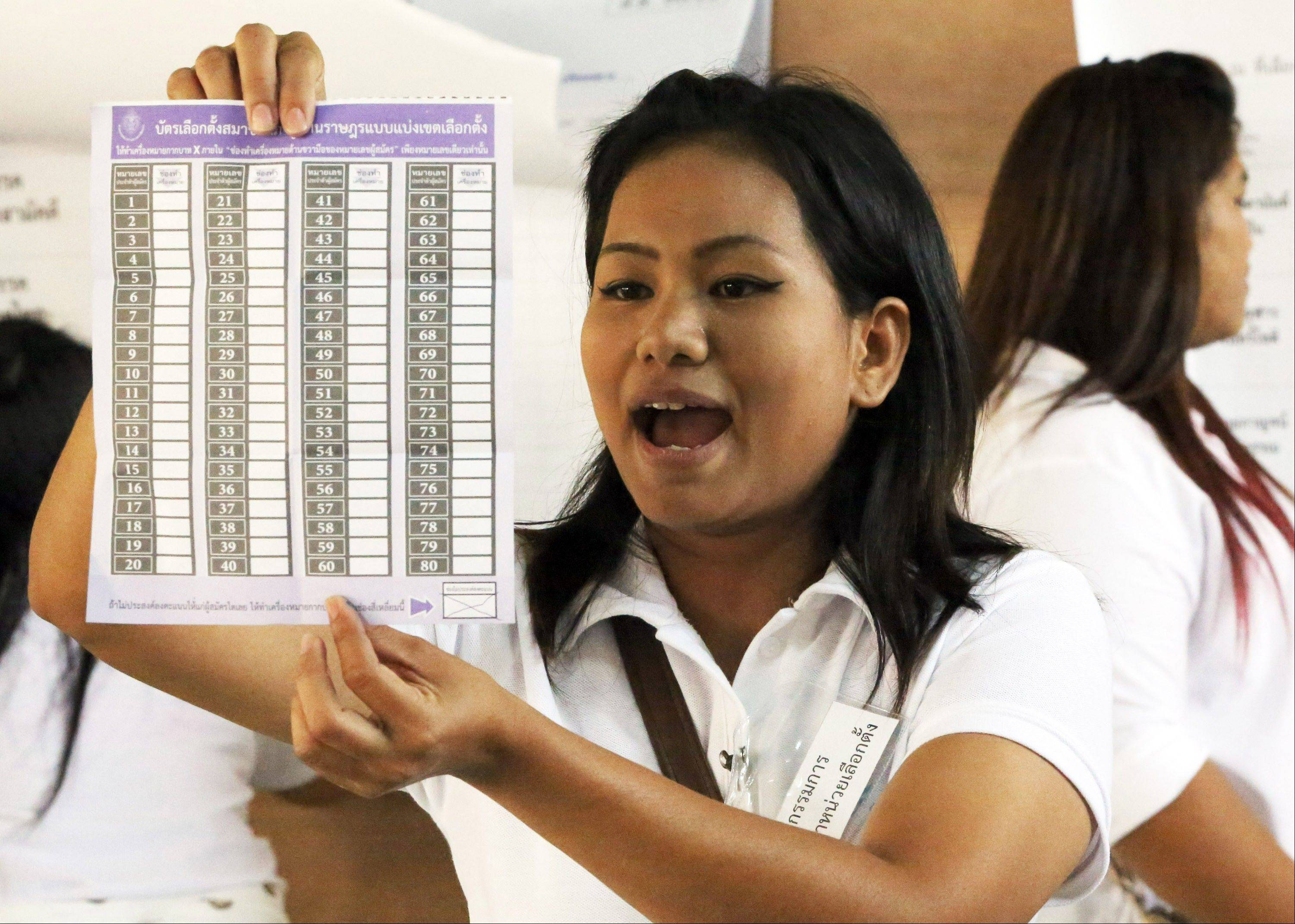 An election official reads a ballot during a vote counting after the general election in Bangkok Sunday. Protesters trying to derail Thailand�s national elections Sunday forced the closure of hundreds of polling stations in a highly contentious vote that has become the latest flash point in the country�s deepening political crisis.