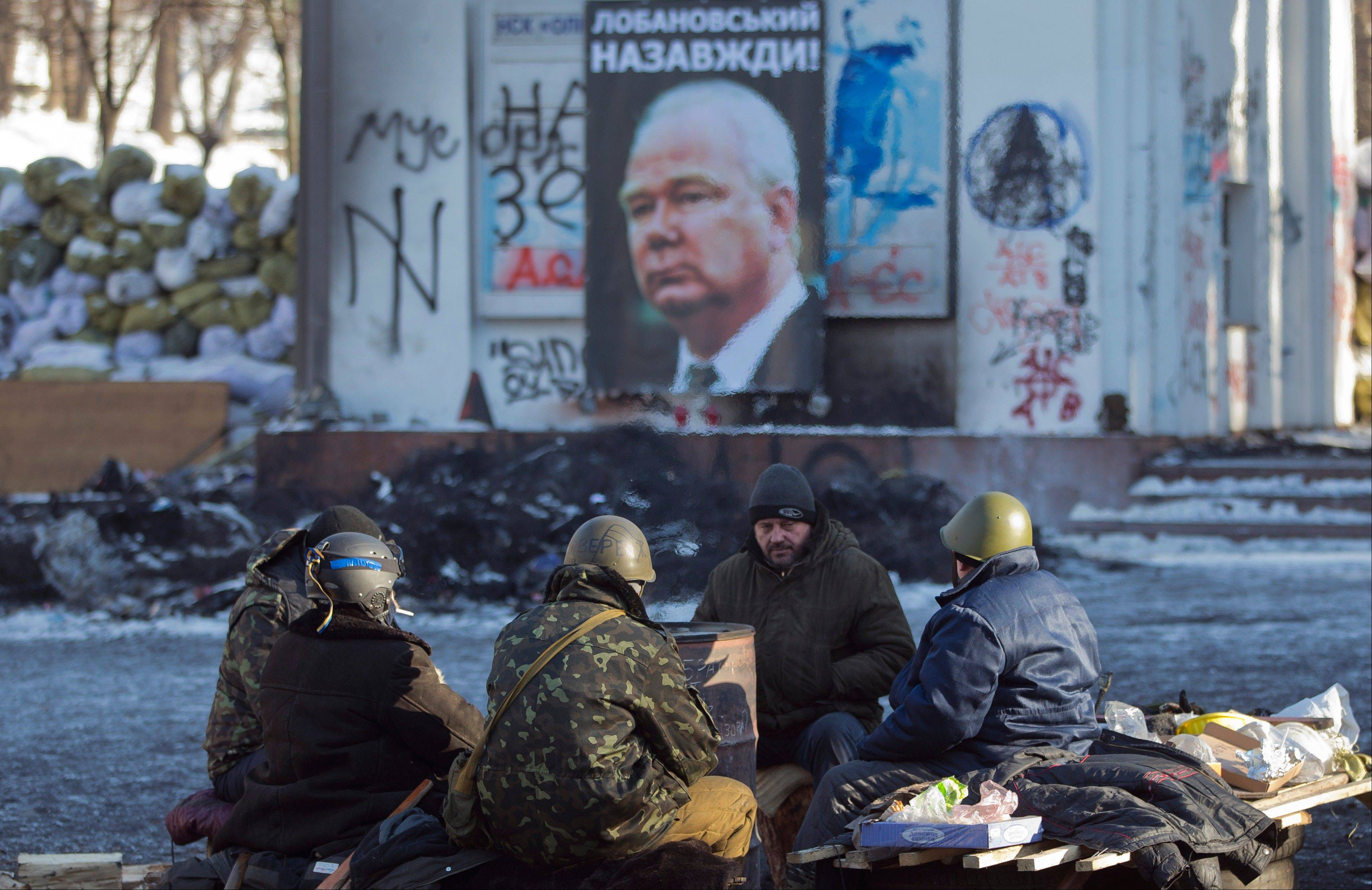 A group of anti-government protesters warm themselves around a barrel near a poster of famous Ukrainian soccer coach and player Valeriy Lobanovskyi, in central Kiev, Ukraine, Sunday.