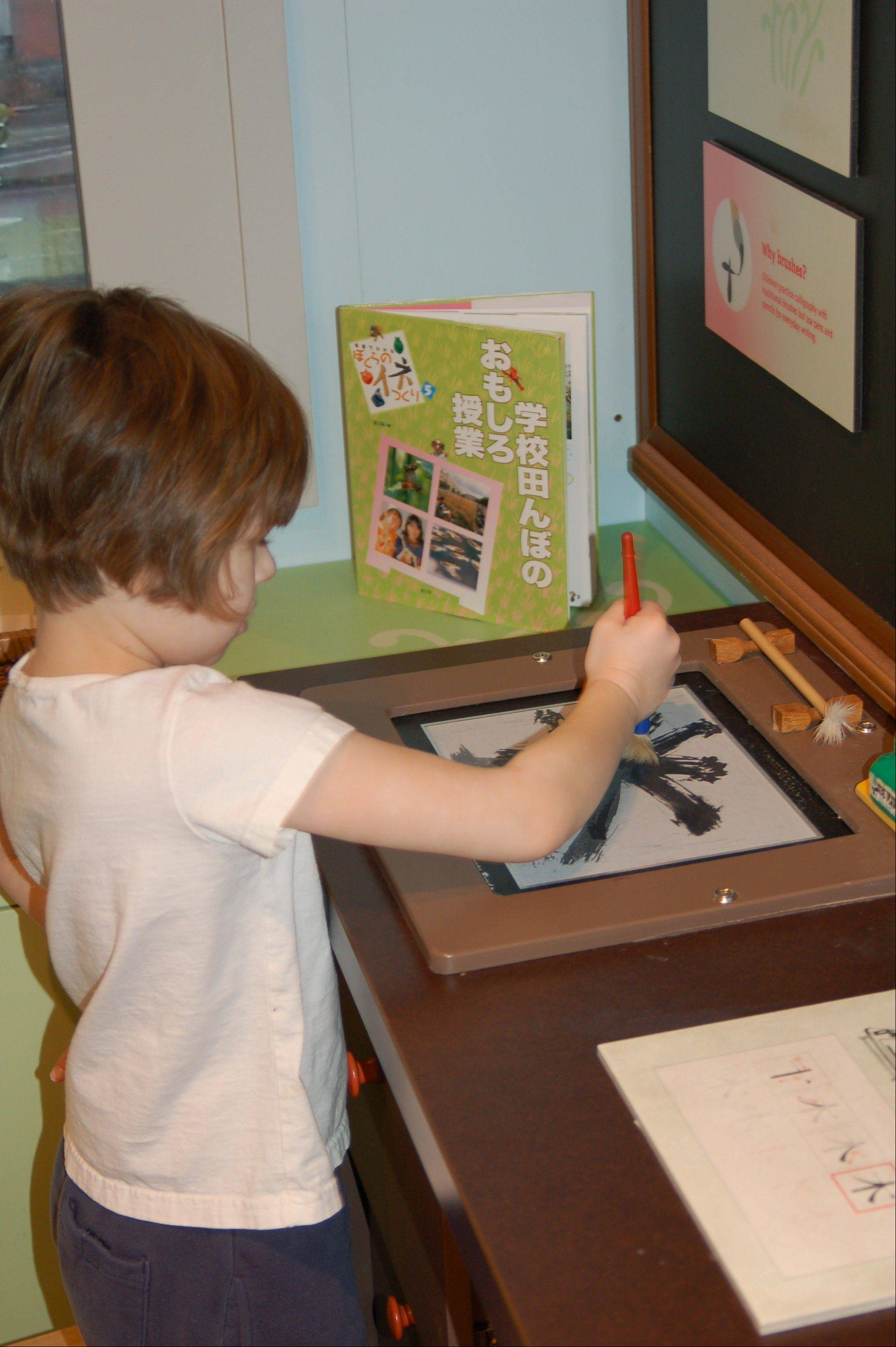 "Visitors learn how to craft letters using the Kanji system of writing in the spring section of the exhibit ""Japan and Nature: Spirits of the Season."""
