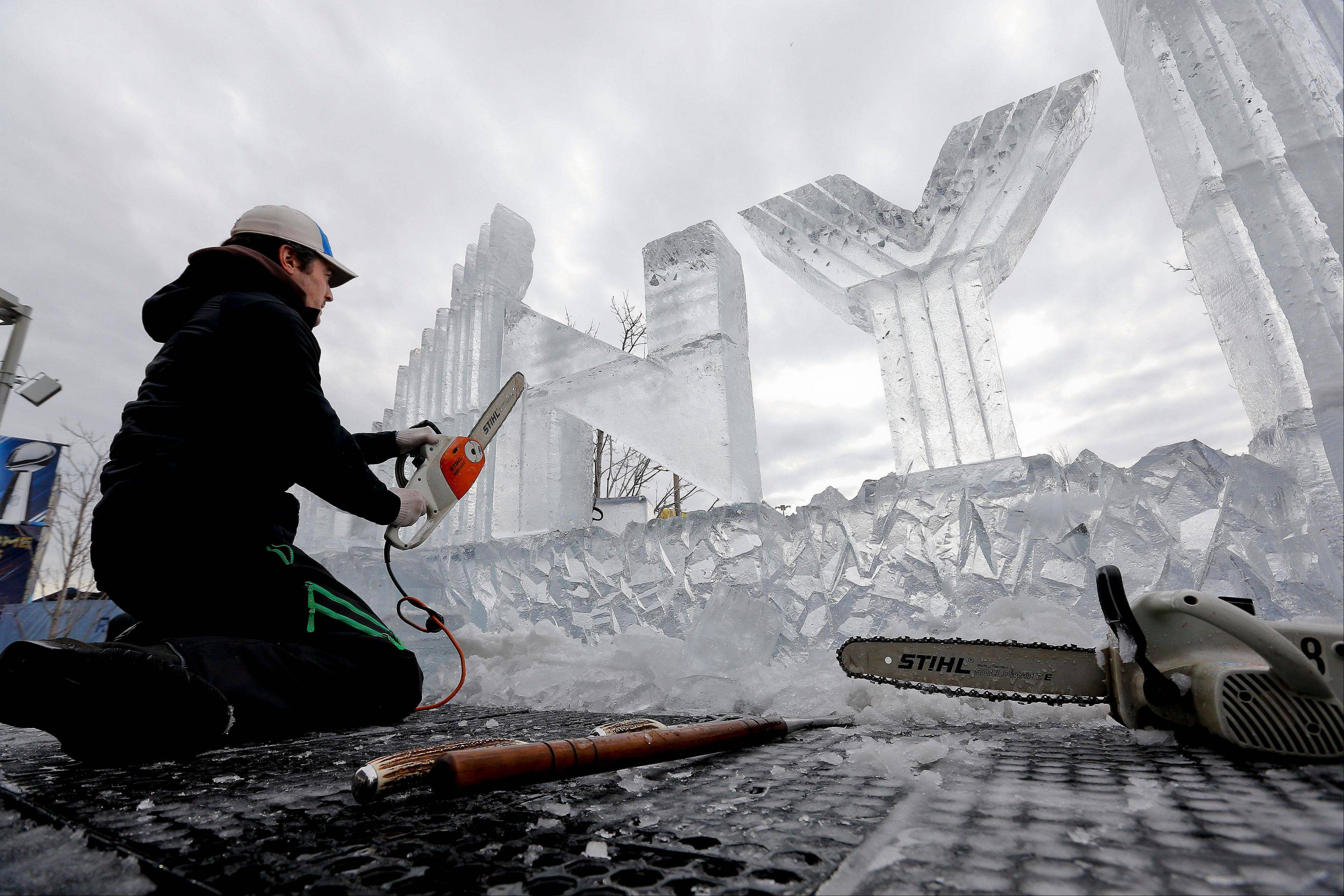 Jeremy Mangan carves an ice sculpture outside the stadium before the start of the NFL Super Bowl XLVIII football game Sunday, Feb. 2, 2014, in East Rutherford, N.J.